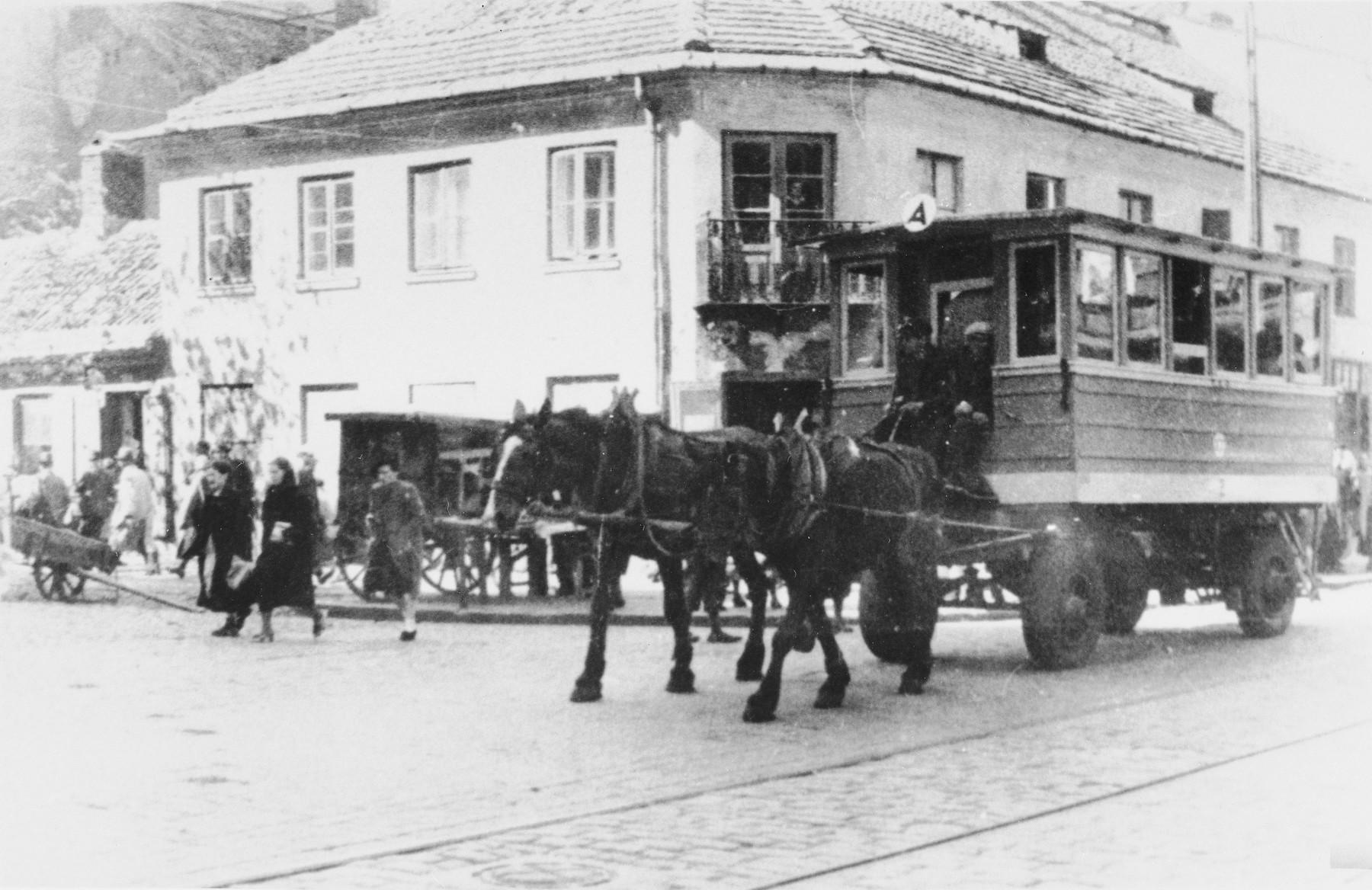 A horse-drawn streetcar runs down a street in the Warsaw ghetto.