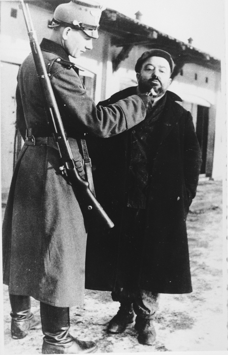 A German policeman publicly humiliates a Jew in the Zawiercie ghetto by shaving his beard.