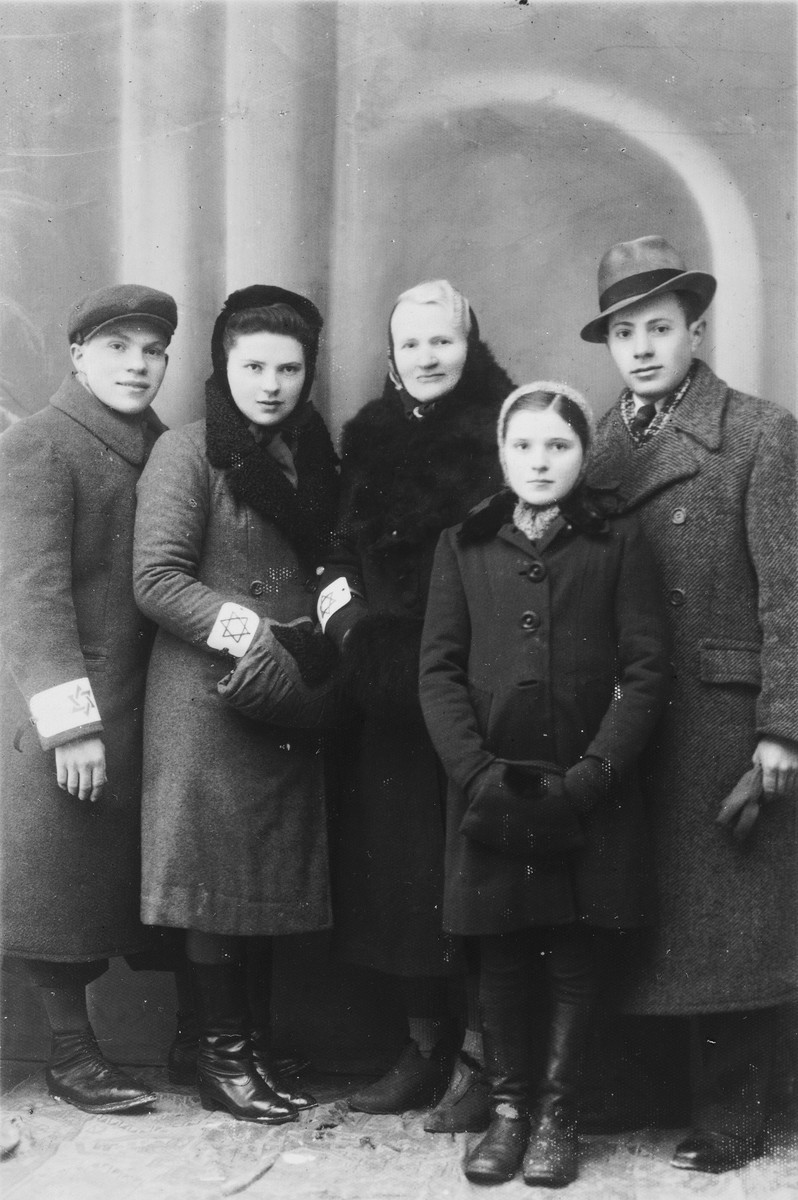 Members of the Kleinhandler family in the Chmielnik ghetto wearing armbands.  Pictured from left to right are Kalman, Bluma and Chaya Kleinhandler, Pesele Moszenberg, and Moshe Kleinhandler.