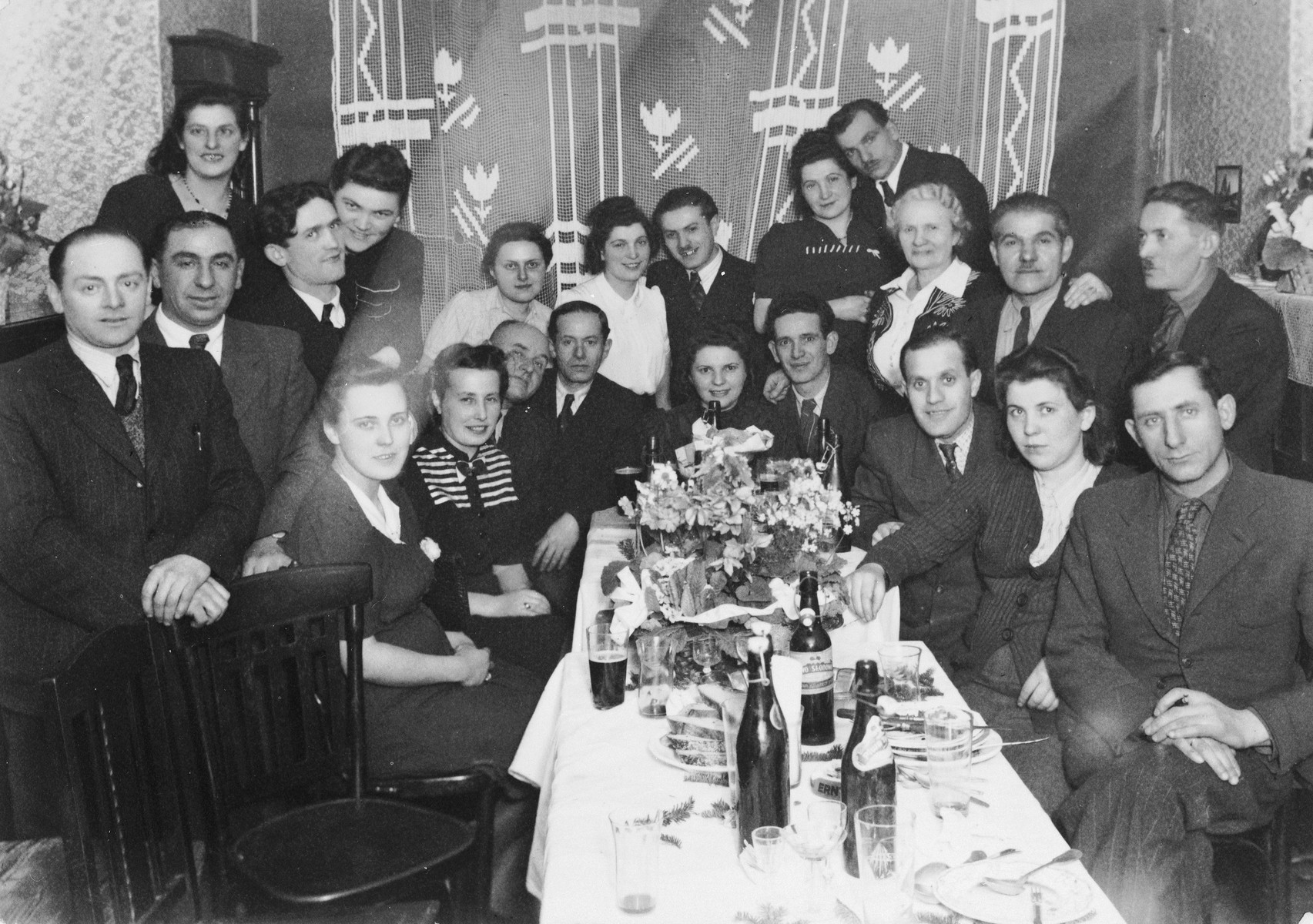 Family and friends of Bluma Kleinhandler and Zygmunt Godzinski celebrate their wedding in Chorzow, Poland.  Among those pictured are Tola Becker (standing eighth from the right), Sara (Zilberberg) Kleinhandler (wife of Moshe, standing seventh from the right), Moshe Kleinhandler (standing sixth from the right), Bluma Kleinhandler (seated at the head of the table), Zygmunt Godzinski (seated next to Bluma), Chaya Kleinhandler (standing third from the right), Chaim Kleinhandler (standing second from the right).