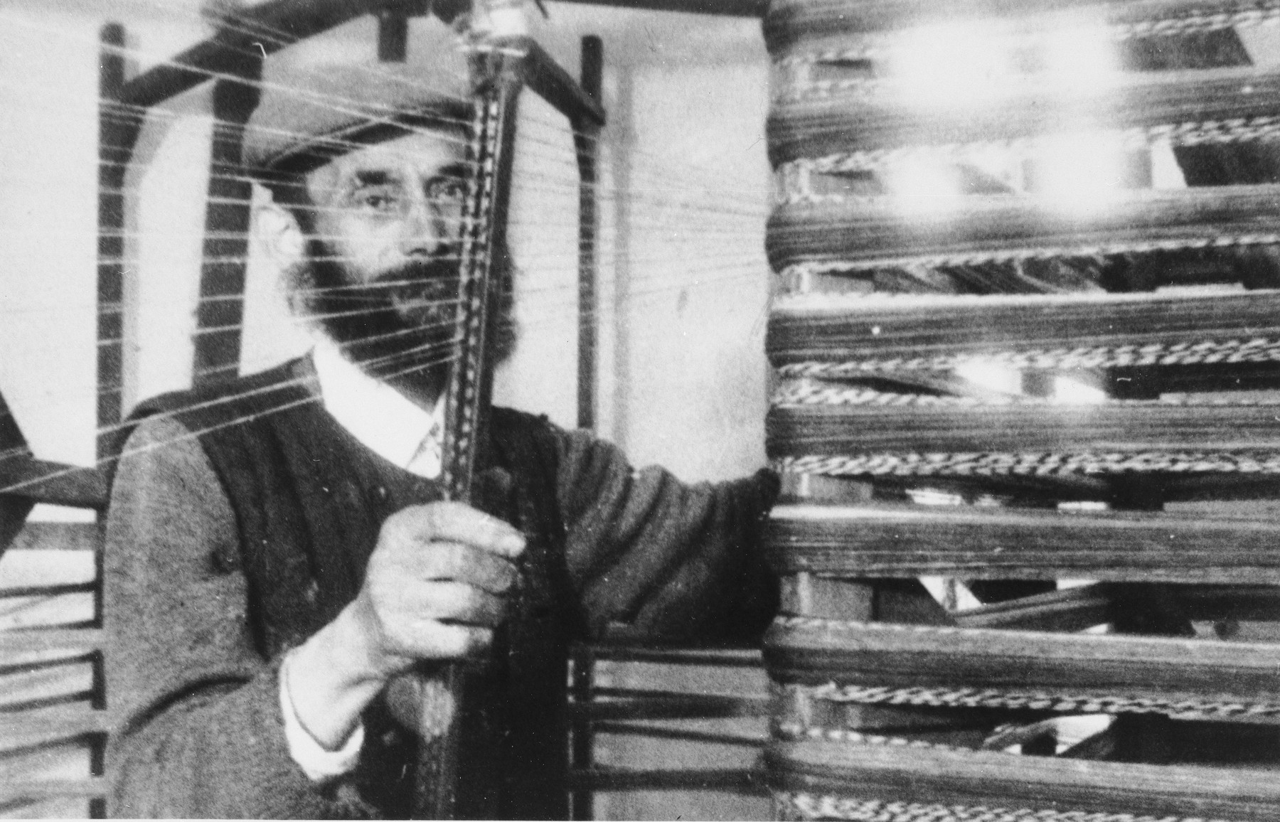 A Jewish man operates a loom in an unidentified ghetto.