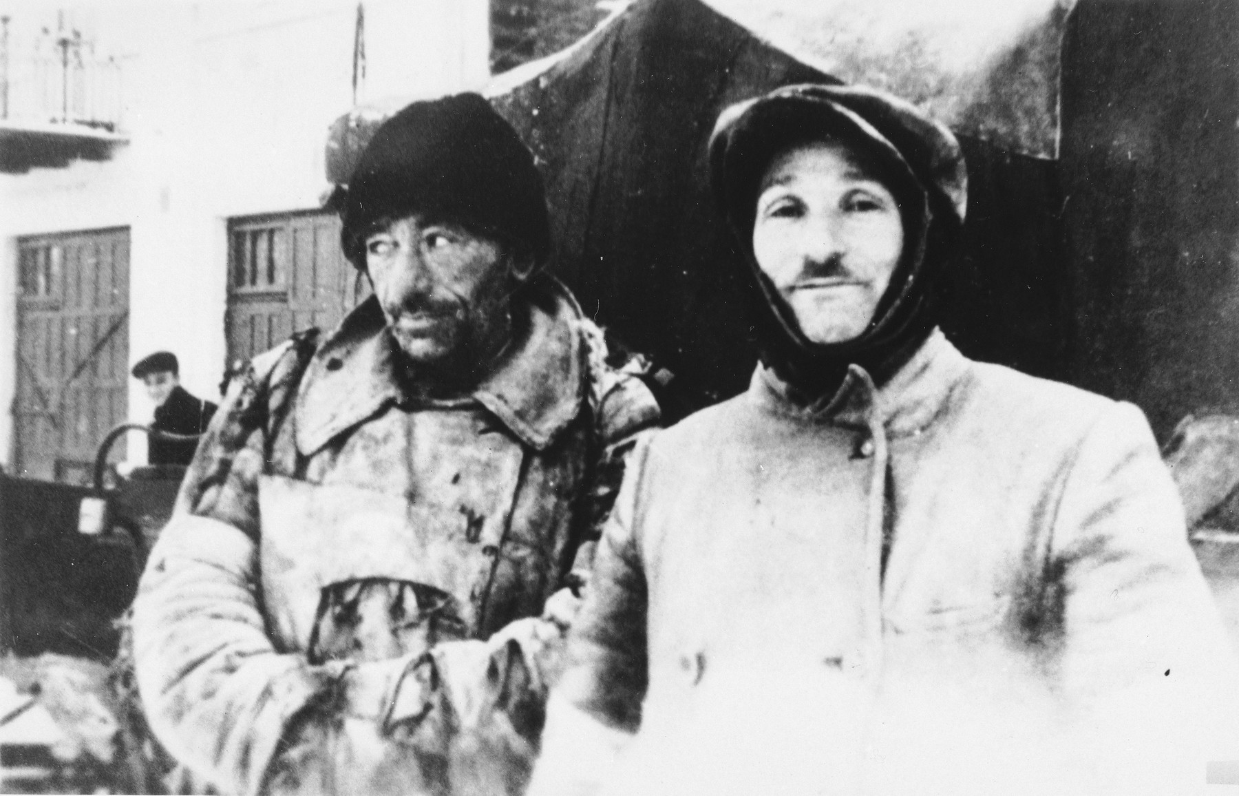 Close-up of two Jewish men wearing overcoats on a street in an unidentified ghetto.