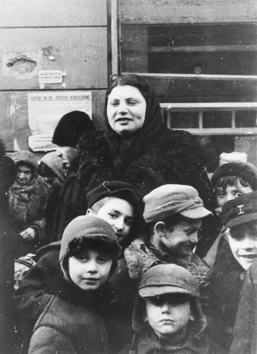 A woman stands behind a group of boys on a street in the Warsaw ghetto.