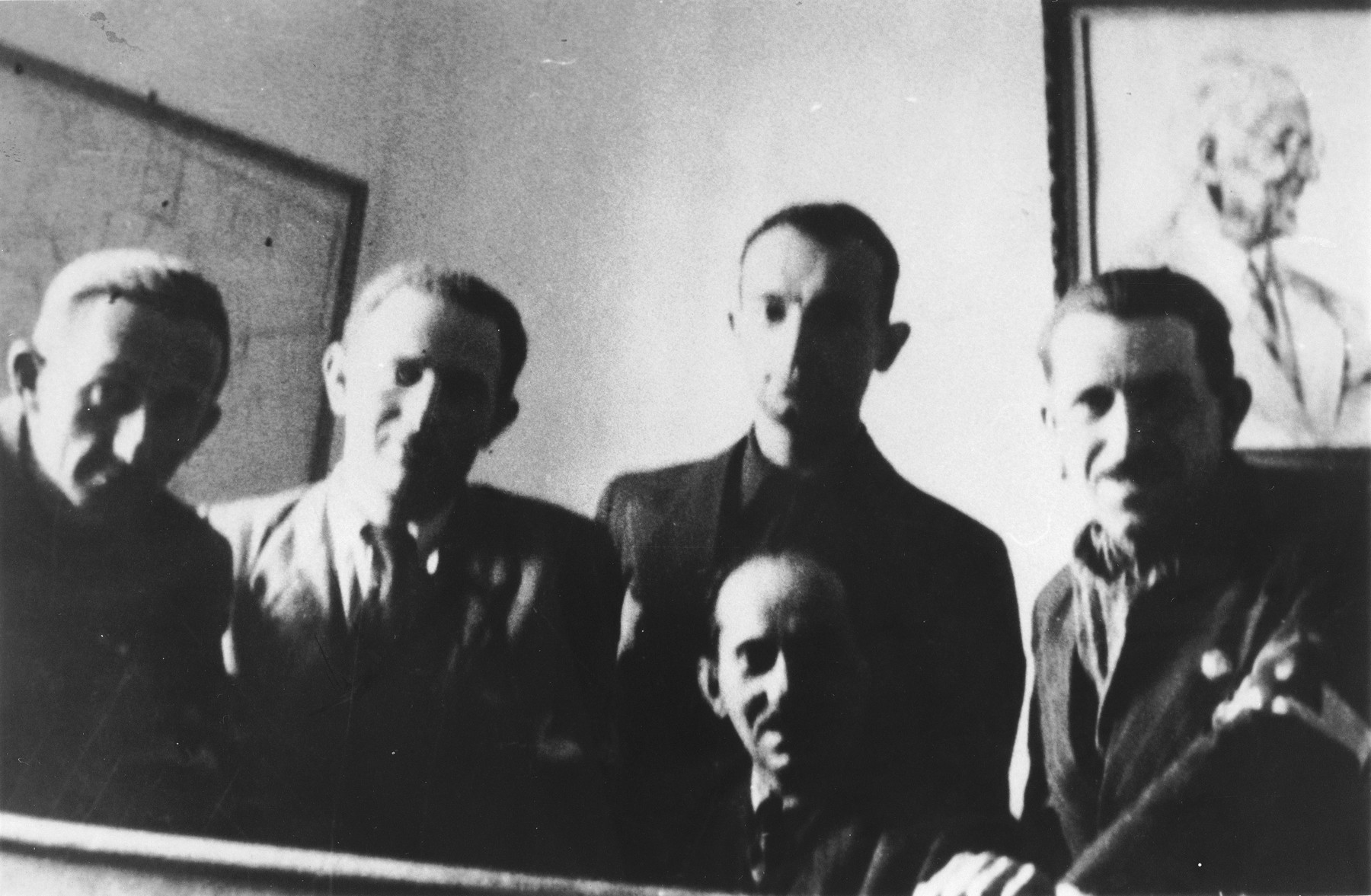 Four members of the Lodz ghetto leadership pose in an office beneath a portrait of Jewish council chairman Mordechai Chaim Rumkowski.