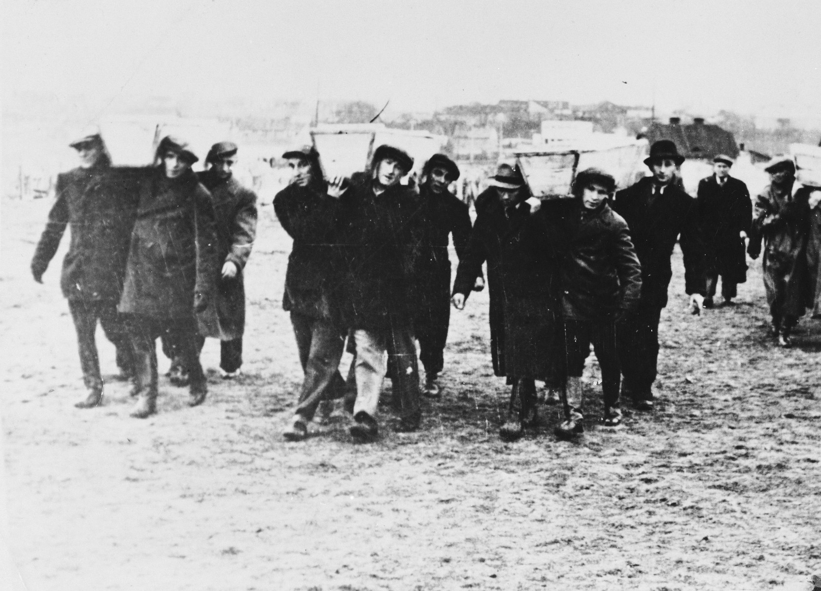 Pallbearers carrying the the victims of the Kielce pogrom, transport the coffins from trucks to the burial site in the Jewish cemetery.