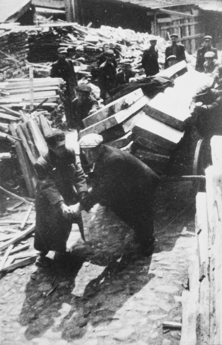 A group of Jewish men haul lumber through what probably is the Lodz ghetto.