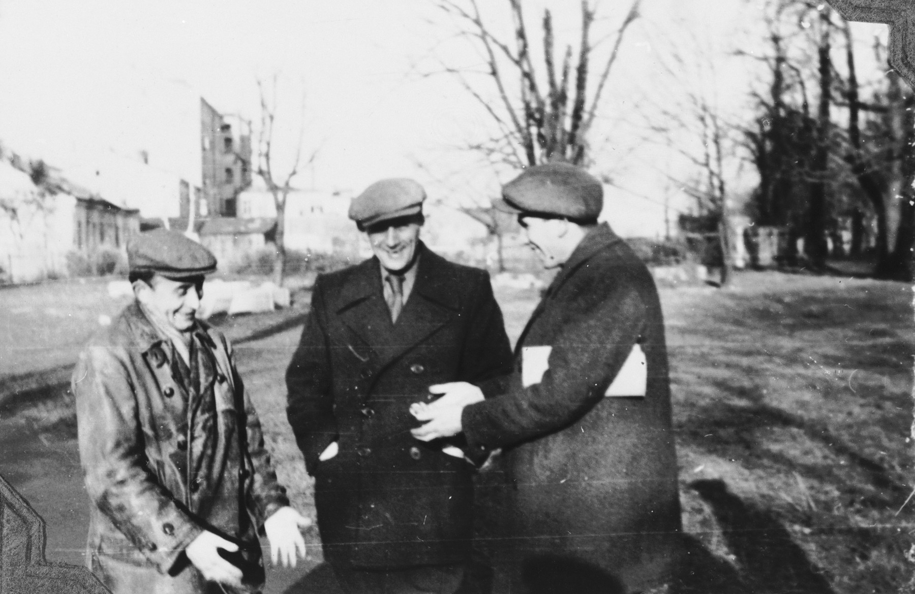 Three Jewish friends converse outside in Kielce.  Among those pictured is Zygmunt Godzinski (right).