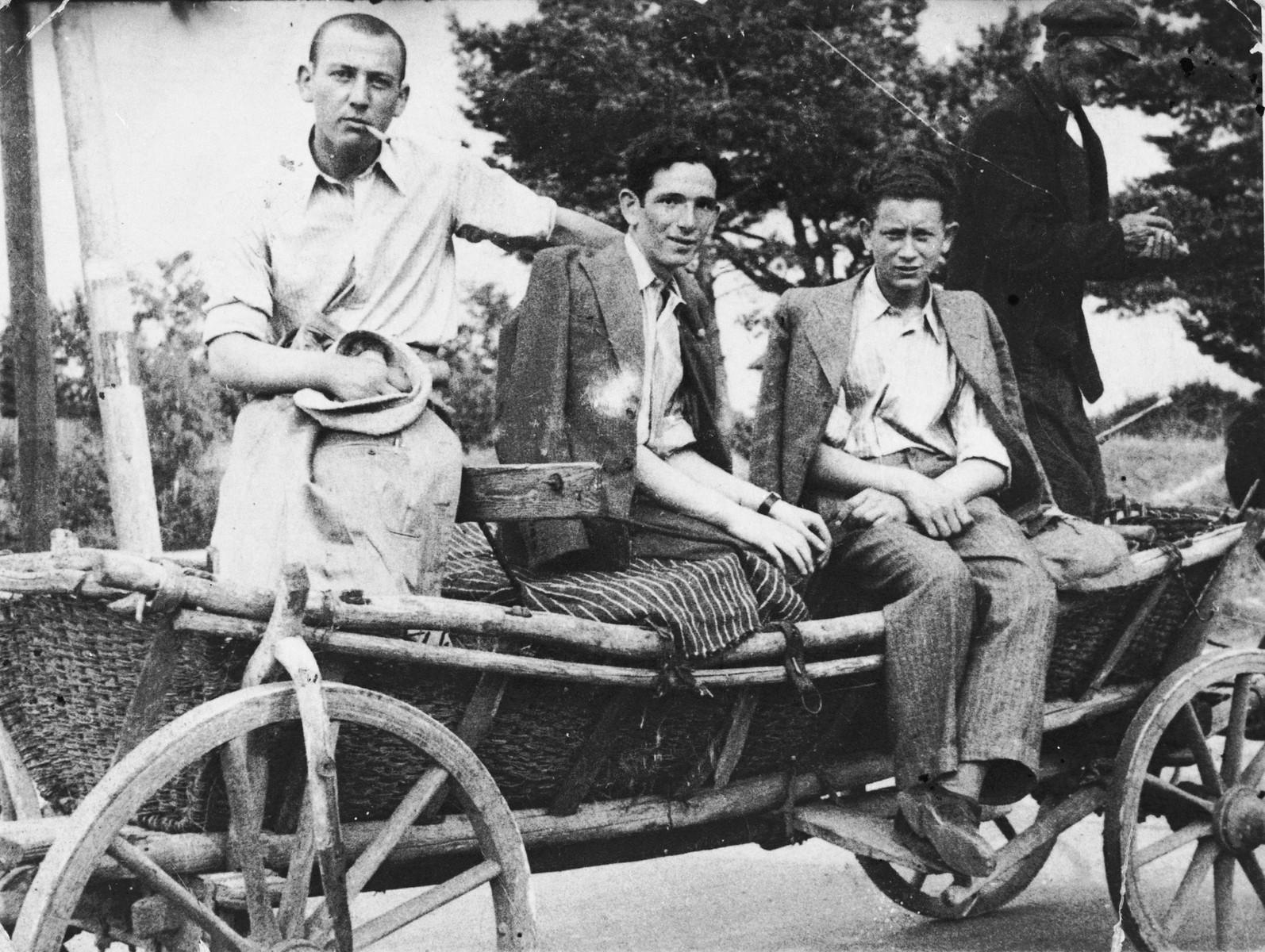 Zygmunt Godzinski (middle) sits with two friends on a horse-drawn wagon in Kielce.