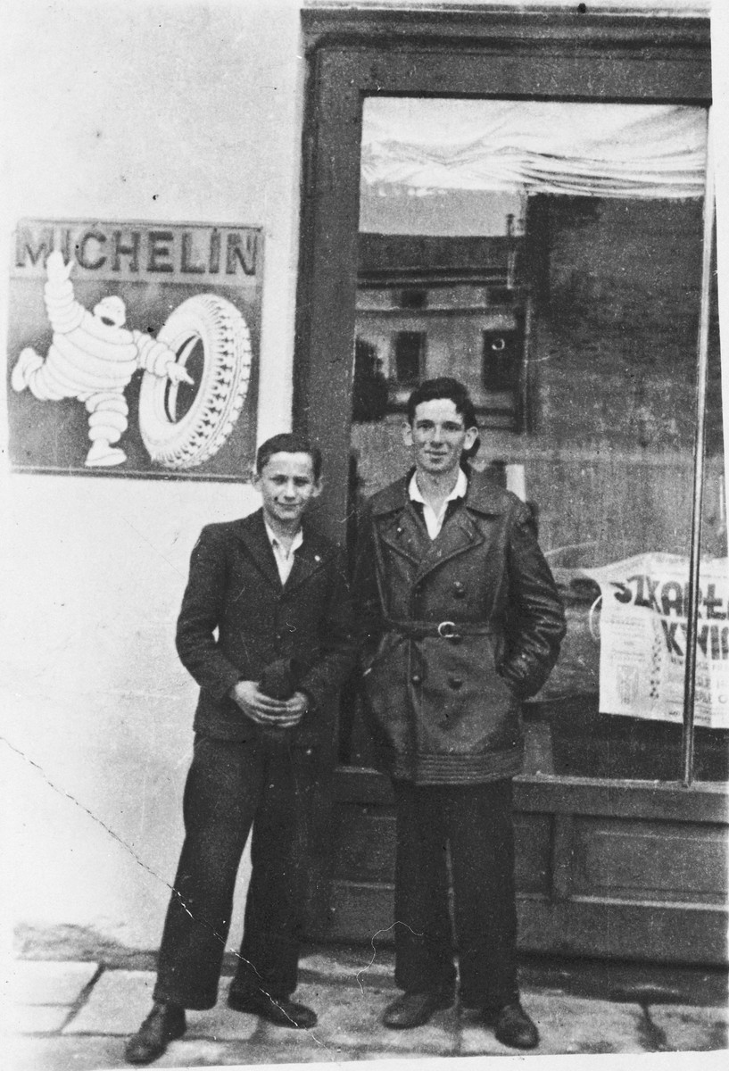 Zygmunt Godzinski (right) poses with a friend outside a business in Kielce.  Behind them is an advertisement for Michelin tires.
