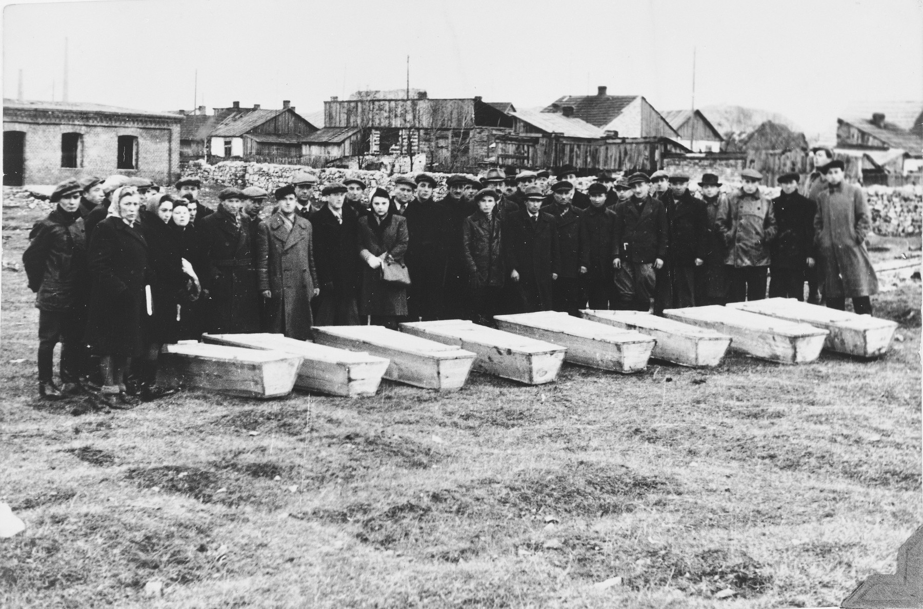 Mourners stand behind a row of coffins at the burial site in the Jewish cemetery for the victims of the Kielce pogrom.