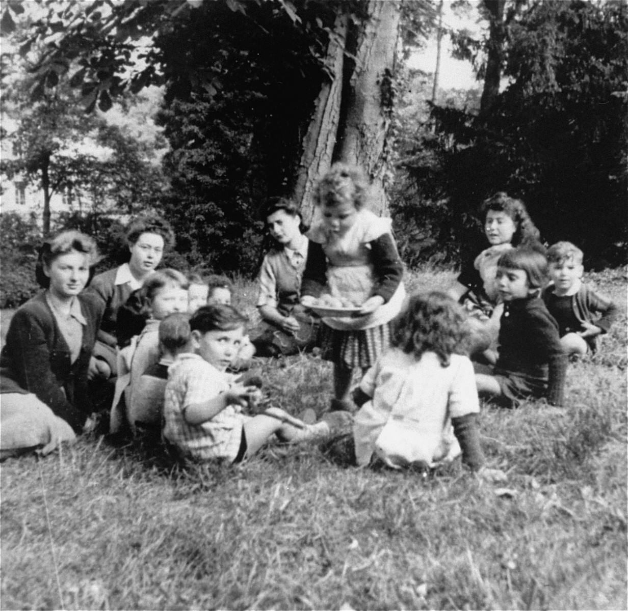 A group of young children sit in a circle on the grass outside the OSE Home in Draveil.