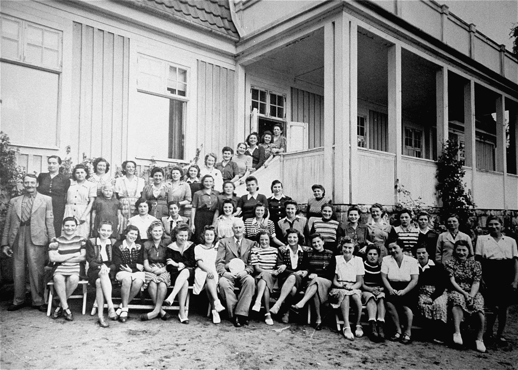 Group portrait of Jewish female survivors of Bergen-Belsen, who were evacuated to Sweden at the end of the war, and are now convalescing at hospital in Stensjoen Nomnekul.  Pictured in the back row, at the base of the stairs and seventh from the right, is the donor's wife, Helen Kaufman.  Originally from Beregasz, in Hungarian-controlled Slovakia, Kaufman was deported to Auschwitz in May 1944.  She was later transferred to Bergen-Belsen, where she was liberated.  Also among those pictured are Barbara (Borbala) Grunstein (third from the left in the front row) and her Ilona Gerendas (second from the left in the first row).