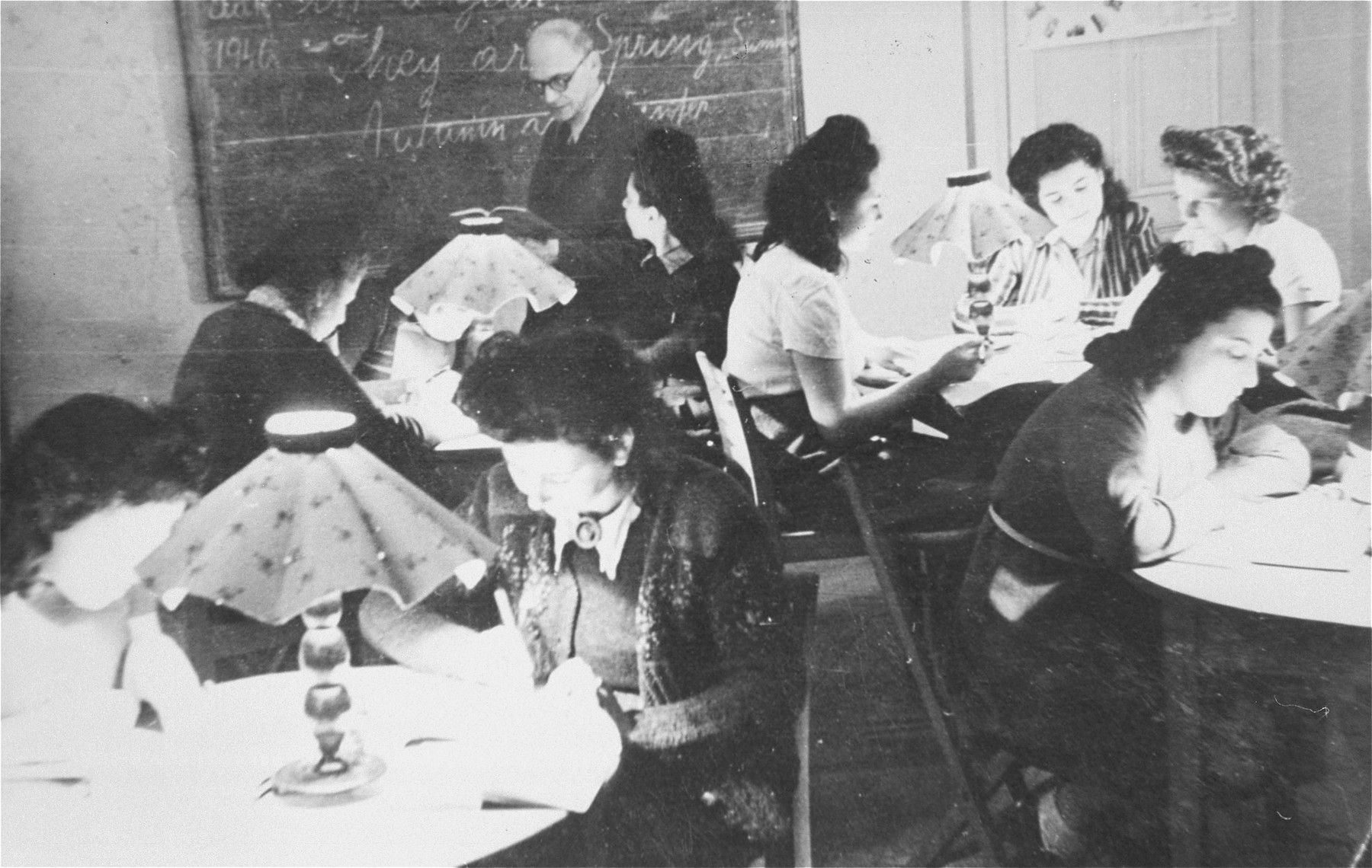 Young Jewish women living at the Le Tremplin children's home study in small groups seated around several tables.
