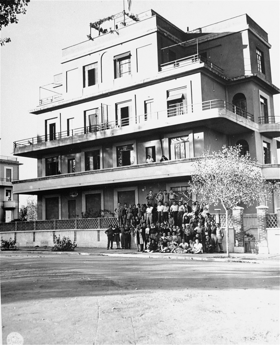 Group portrait of Jewish displaced youth in front of the villa in Rome where they are living.  The displaced persons center is being run jointly by the JDC (Jewish Joint Distribution Committee) and UNRRA (United Nations Relief and Rehabilitation Administration).  Among those pictured are Benjamin Brooks, a representative of the JDC, and Antonio A. Lovieri and Vlad F. Ratay, representatives of UNRRA.