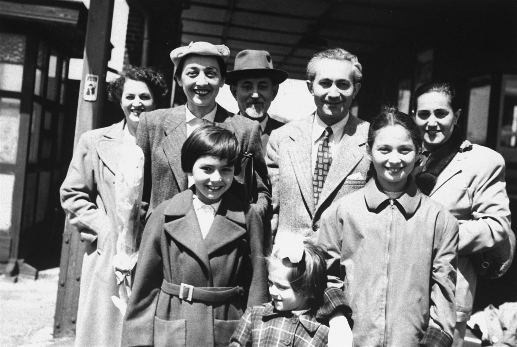 Group portrait of the Ament family at the train station in Antwerp prior to their departure for the United States.  Pictured are: First row, left to right are Jeanine Ament , Eleonore Ament and Miriam Matzner.  Back row (left to right):  Paula  Ament Schwalb, Mania Ament, Chaim-Shia Ament, Marian Ament and Rosia Ament Molkner.