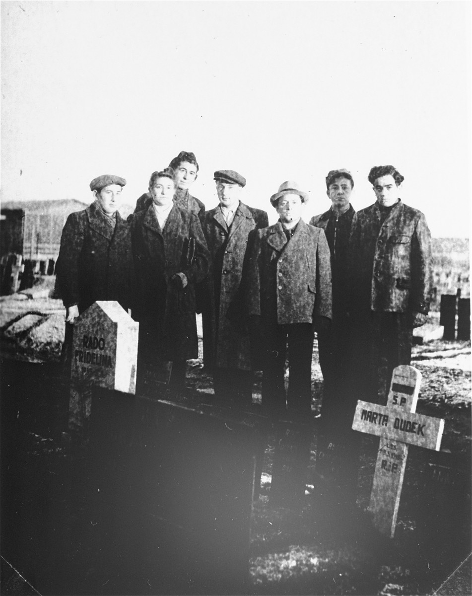 Members of Kibbutz Buchenwald pose next to a memorial or gravemarker at a cemetery.