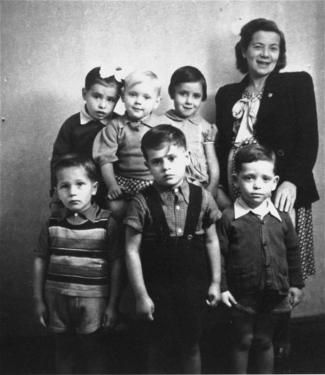 Bina Halperin poses with a group of six Jewish orphans at a children's home in Austria run by the American Joint Distribution Committee. These children were part of a larger group of twenty to thirty orphans who were removed by Bina Halperin from a convent in Poland were they had been hidden during the war.