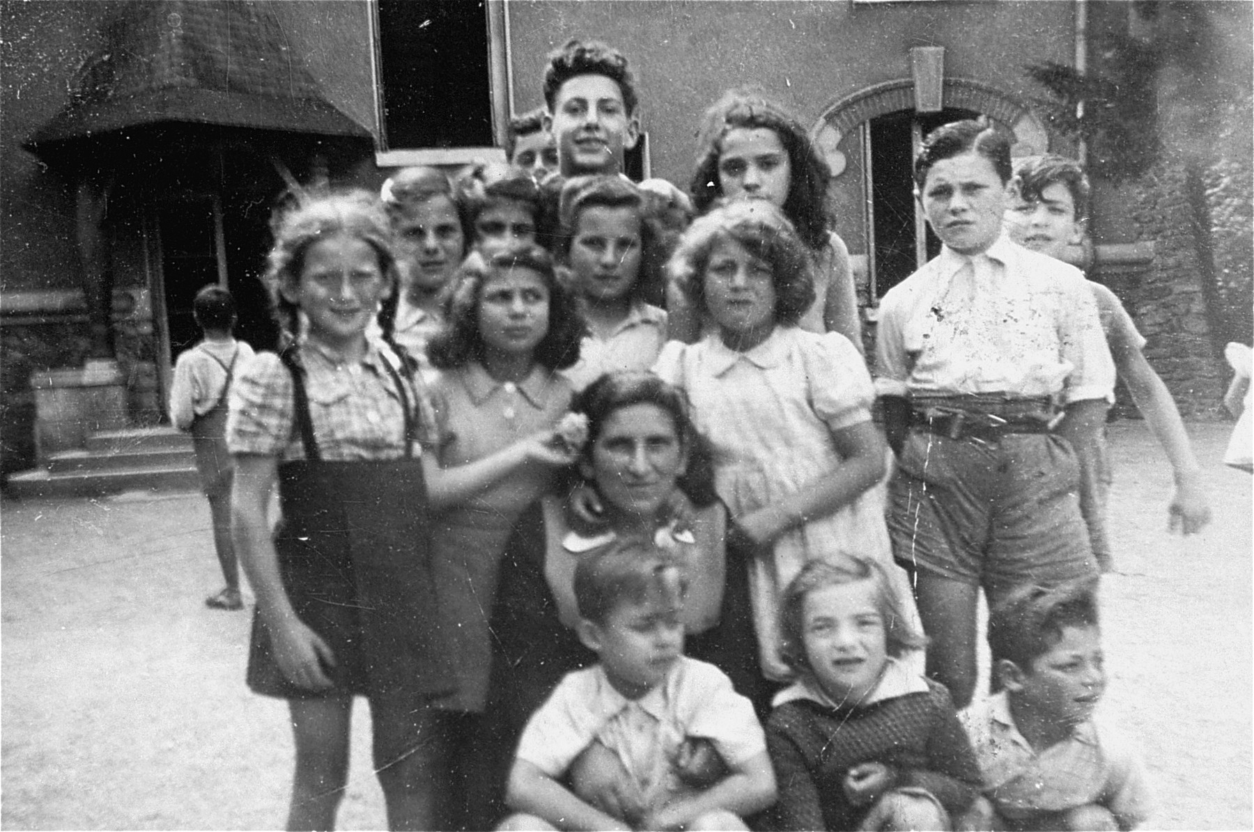 Group portrait of Jewish children in an OSE (Oeuvre de Secours aux Enfants) home in Draveil, France.    Hemine Katz, who took care of these children, is pictured in the middle of the group.  Felice Zimmern is pictured crouching in the front row between two boys.