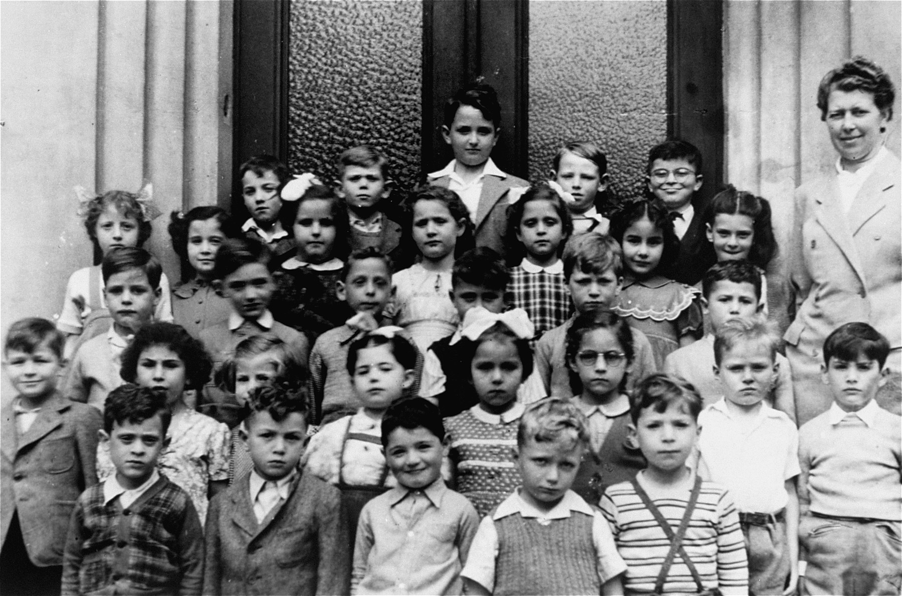 Group photo of the first grade class at the Tachkemoni Jewish private school in Antwerp.    Jeanine Ament, is pictured in the second row from the front, fourth from the right.  The teacher is Mme Boucher.