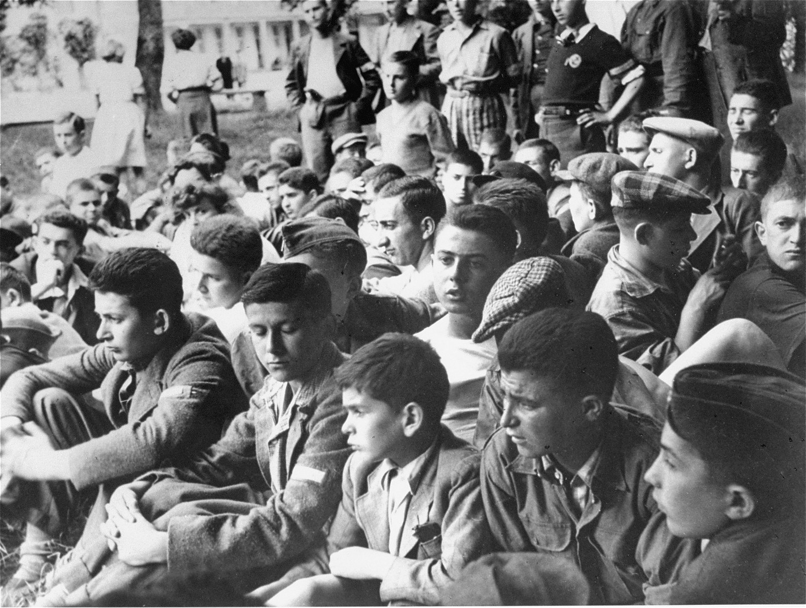 Jewish youth who were members of the Buchenwald children's transport sit outside at a meeting in the Ecouis children's home.  The older teenager in the center is Jochan Ranz from Bedzin.