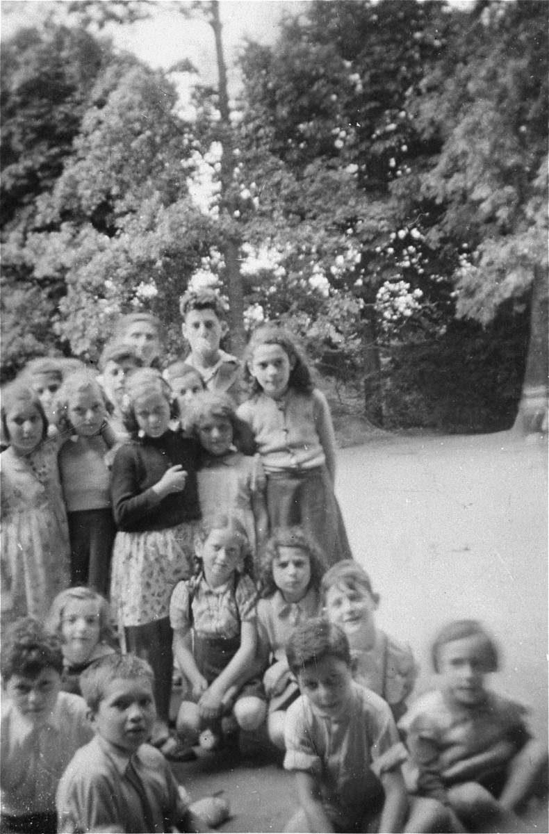 A group of DP children at Draveil. Eric Cahn is in the lower left hand corner.  Felice Zimmern is pictured third person, on the left (sitting on the ground, behind two boys).