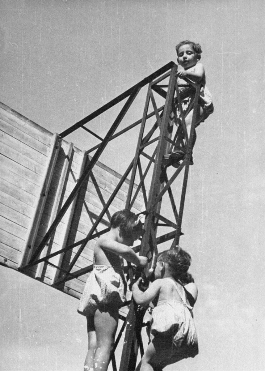 Children climb a jungle gym in the playground at the Le Petit Monde children's home near Paris.