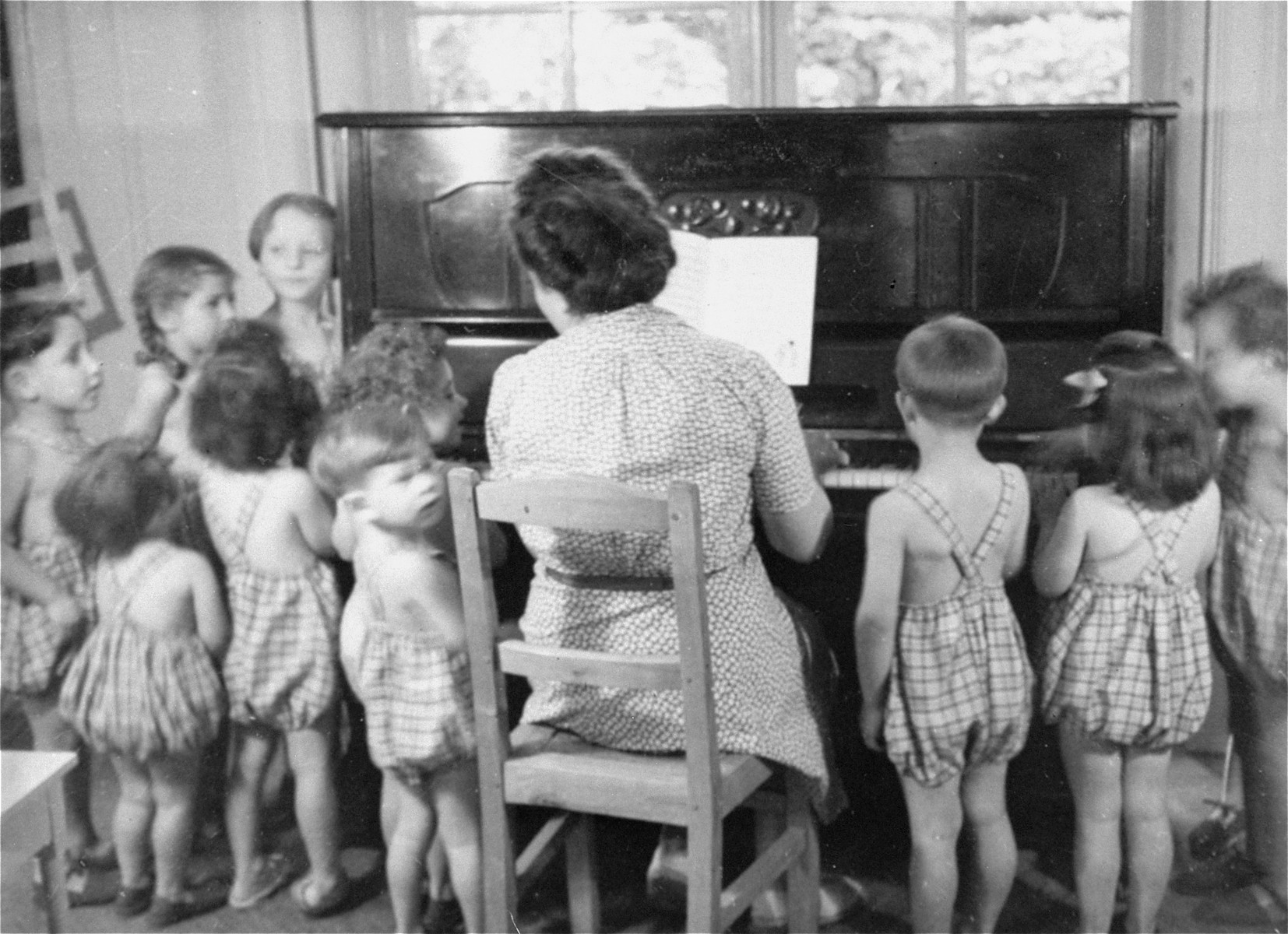 Simone Weil plays the piano for the children at the Le Petit Monde home near Paris.