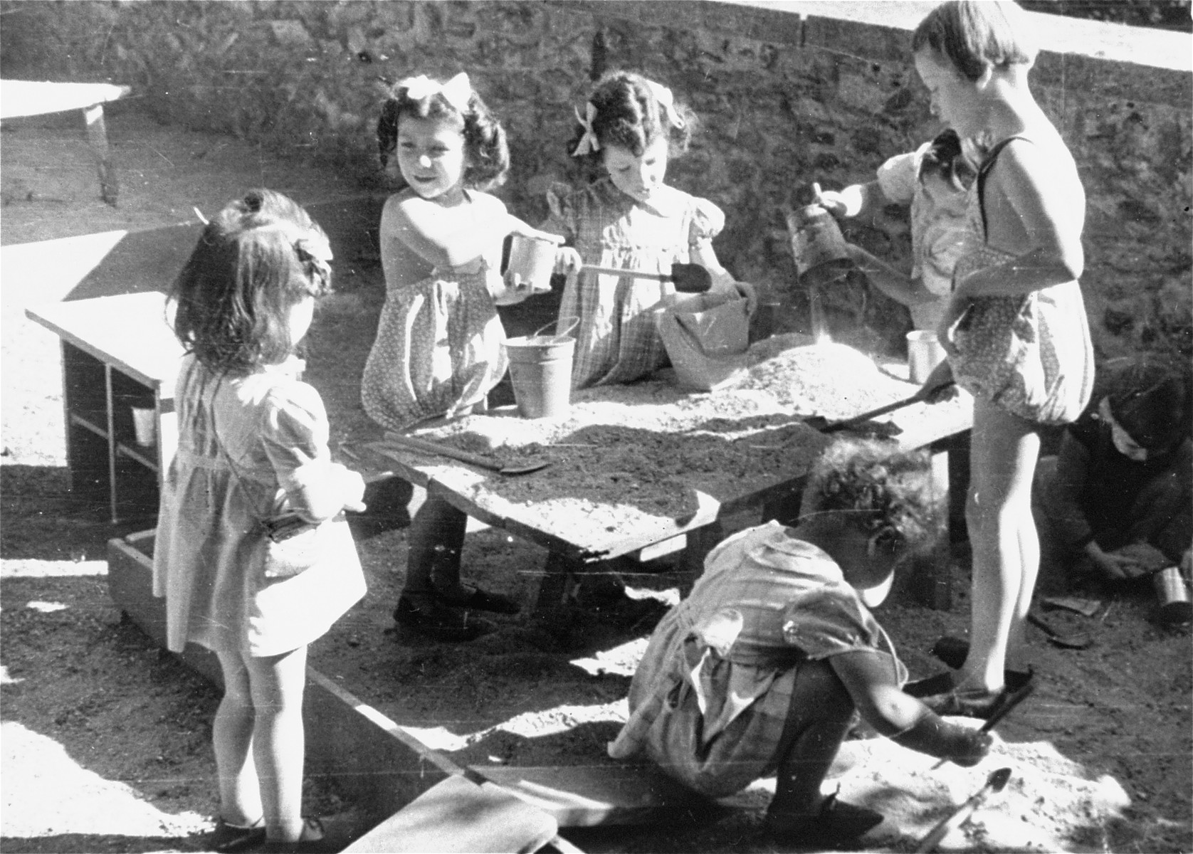 Young Jewish children play in a sandbox at the Le Petit Monde children's home near Paris.
