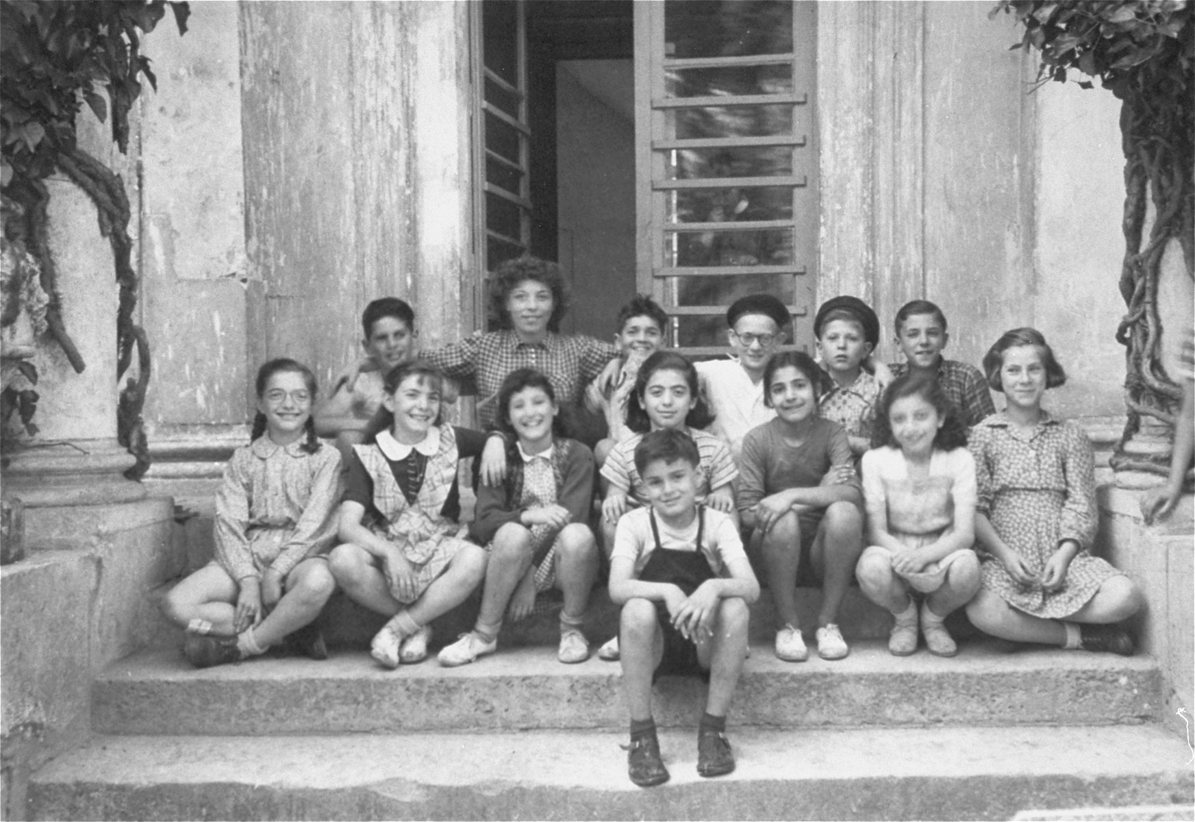Group portrait of children at the OSE (Oeuvre de Secours aux Enfants) children's home at the Château de Vaucelles in Taverny.   Felice Zimmern is seated in the first row, far left and her sister Beate is seated next to her (second from the left). Sitting next to them are Francine and Edmee.  At the end of the girls' row is Lise Behar. Seated in the back is the counselor Helene Ekayser.  The boy second from the right is  Leon Bretmel.