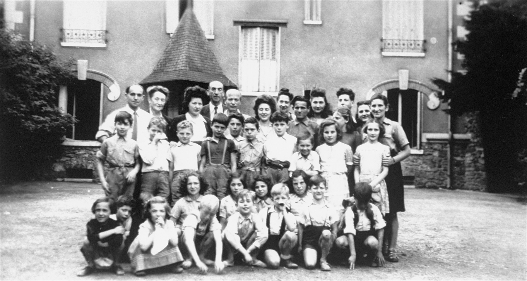 Group portrait of Jewish children in an OSE (Oeuvre de Secours aux Enfants) home in Draveil, France.    Hemine Katz, who helped take care of these children, is pictured in the back row, at the far right.  Felice Zimmern is the third person in the first row, on the left, kneeling and holdng a white handkerchief,.