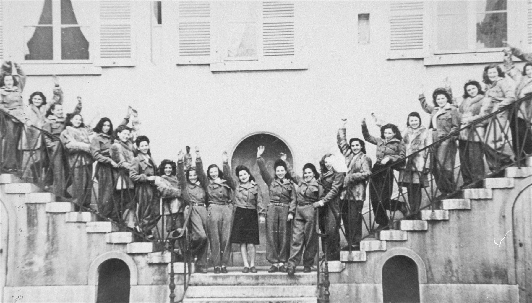 Young Jewish women living at the Le Tremplin children's home pose waving on the front staircase.