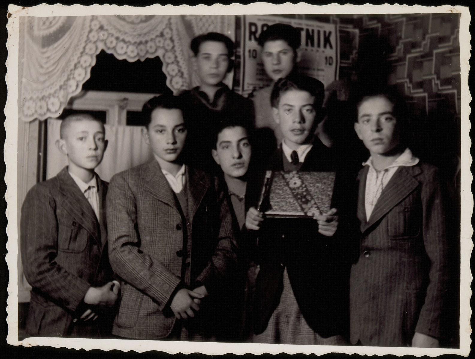 Fishke Shlanski receives an album with the pictures of his friends prior to his immigration to America.  Standing from right to left: Moshe Ginunski, Fishke Shlanski, Zalman Zubitzki, unknown, and Bezalel Charney.  Standing on top from right to left: Tuvia Blacher and Benjamin Shlanski.
