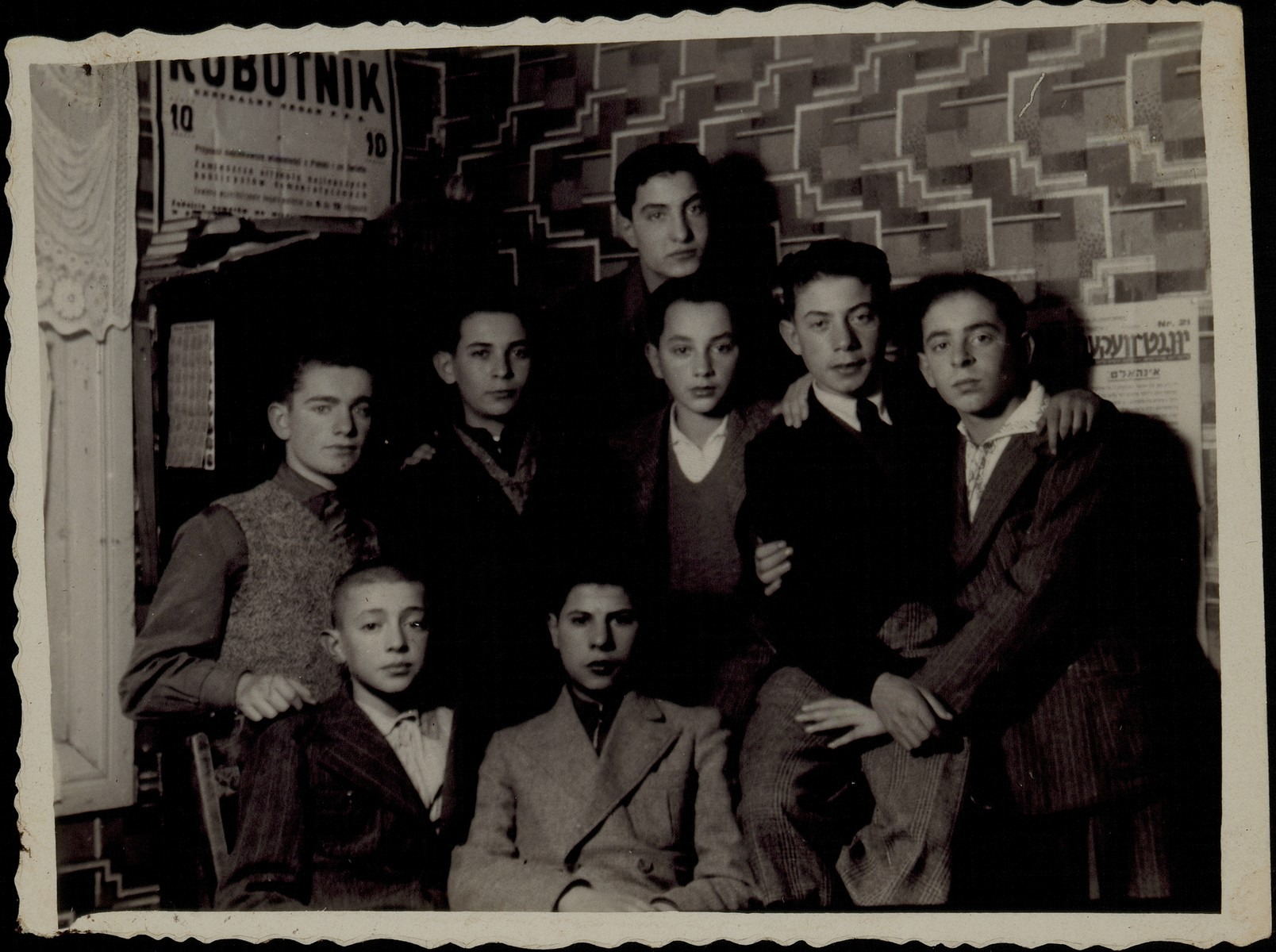 A group of teenage boys gather in a room in front of  posters tacked to the wall.  Sitting from right to left: Tuvia Blacher and Bezalel Charney.  Middle row from right to left: Moshe Ginunski, Fischl Shlanski, unknown, Benjamin Shlanski, unknown.  Zalman Zubizki is on top.    The Shlanski brothers imigrated to America. All the other boys in the photo were murdered in the September 1941 massacre.