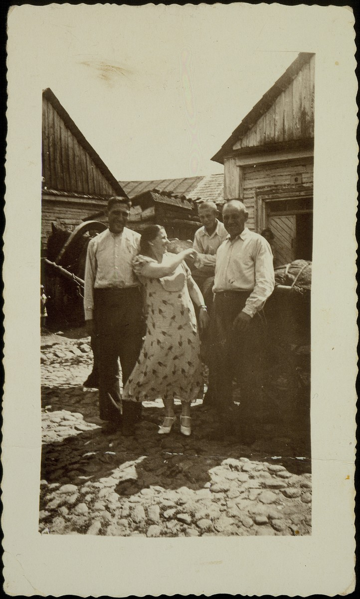 "Vilna coachmen, Zelig and Yitzhak Shlankski, stand beside a loaded wagon in their backyard on the ""Rabbi's Lane"" (Dem Rov's Gessele"").  Also pictured is Mrs. Seagan and Zelig's son Fischl. Zelig and Fischl immigrated to America; Mrs. Seagan to Australia.  Yitzhak was murdered by the Germans in the September 1941 mass killing action in Eisiskes.  The photograph was taken by a visiting American relative."