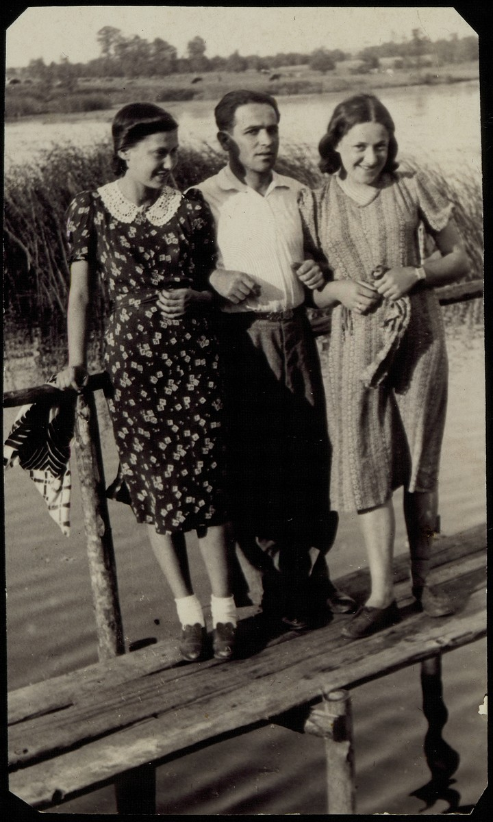 Three young people stand on a wooden bridge in Eisiskes.    From left to right are Feigele Blacher, Pessah Cofnas and his wife Rivka.  Feigele was murdered during the Holocaust.  Pessah and Rivka Cofnas survived in Siberia.