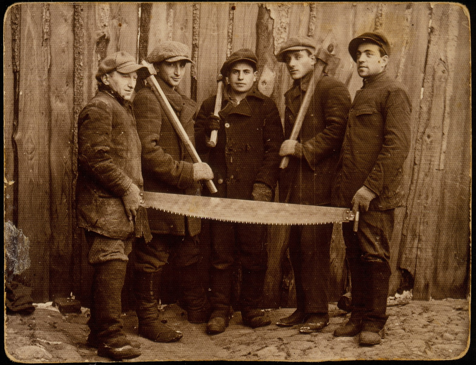 Five young Jewish men who are members of a kibbutz hachshara (Zionist collective) pose holding tools at a logging company in Oczmiana, where they are working to learn the trade and finance their collective.  Among those pictured is Yehiel Blacharowicz (left) from Eisiskes.  He was killed by the Germans during the September 1941 mass shooting action in Eisiskes.