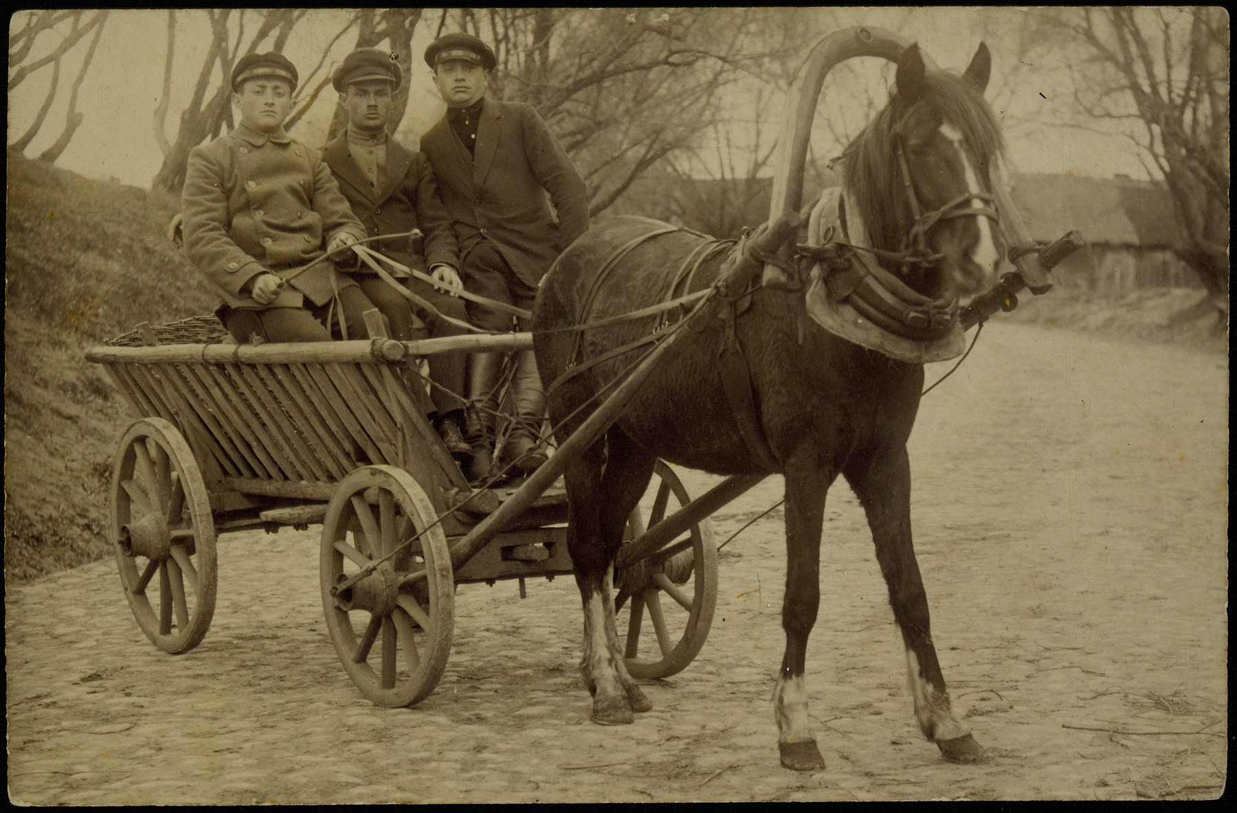 "A Levin, an Eishyshkian coachman, steers a horse-drawn wagon accompanied by two friends.  The photo is inscribed in Hebrew ""For a lasting memory, I am giving my photo to the beautiful maiden, Rashi Deguchinski, from the town of Eisiskes: Better one old lover than two new ones; better a close neighbor than a distant brother."""