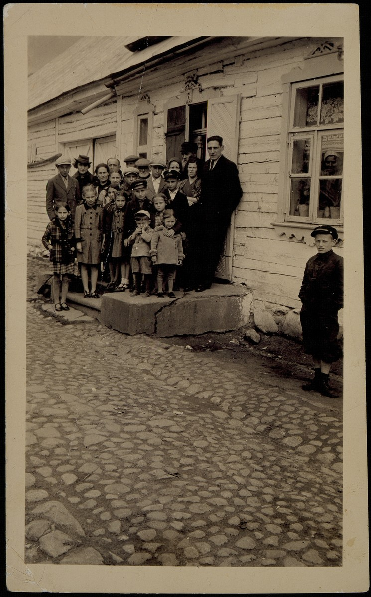 The Shlanski family poses on the steps of its house during a vist of the two Shlanski brothers Morris and Louis from America.   Man standing at the far right is Isaac Shlanski and his wife Devorah is on his left.  The man with a beard in the back center is Avraham-Mordekhai Shlanski, father of Morris and Louis.  Fischl Shlanski (son of Rose and Zelig) is standing in the back at the far left. Second from left is Paike Shlanski Schwartz visiting from America.  Rose Shlanski is standing third from left with her daughter Hayya in front of her.