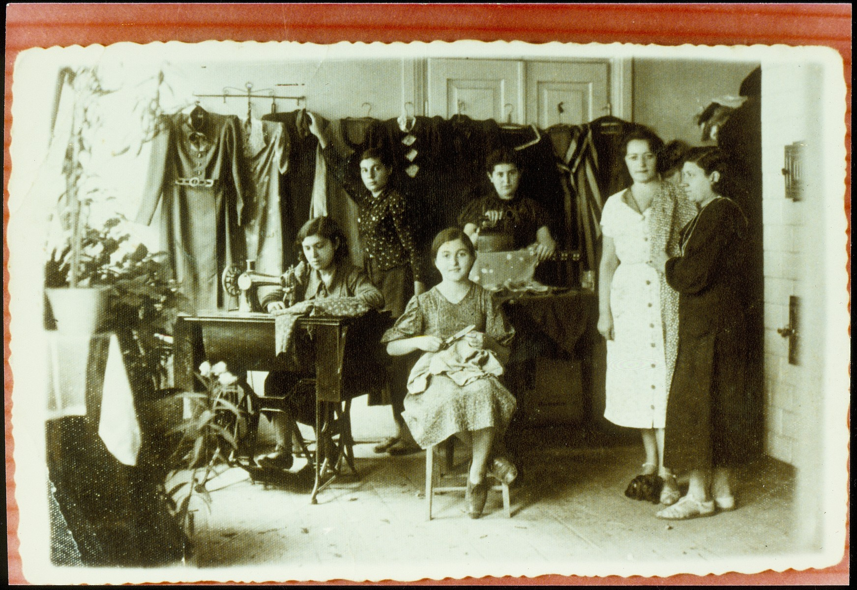 Young women sew in the workshop of master seamstress, Rochel Szulkin.  From right to left are Rochel Slonimski (who rented the workshop to Szulkin), Gittke Demitrowski, Beileh-Rivkeh Radunski, Sara Jankelewicz, and Szulkin's niece, Gitta Politacki at the sewing machine.  Gitta and Sarah survived the war in the Soviet Union; all the others were murdered in the September 1941 mass killing action in Eisiskes.