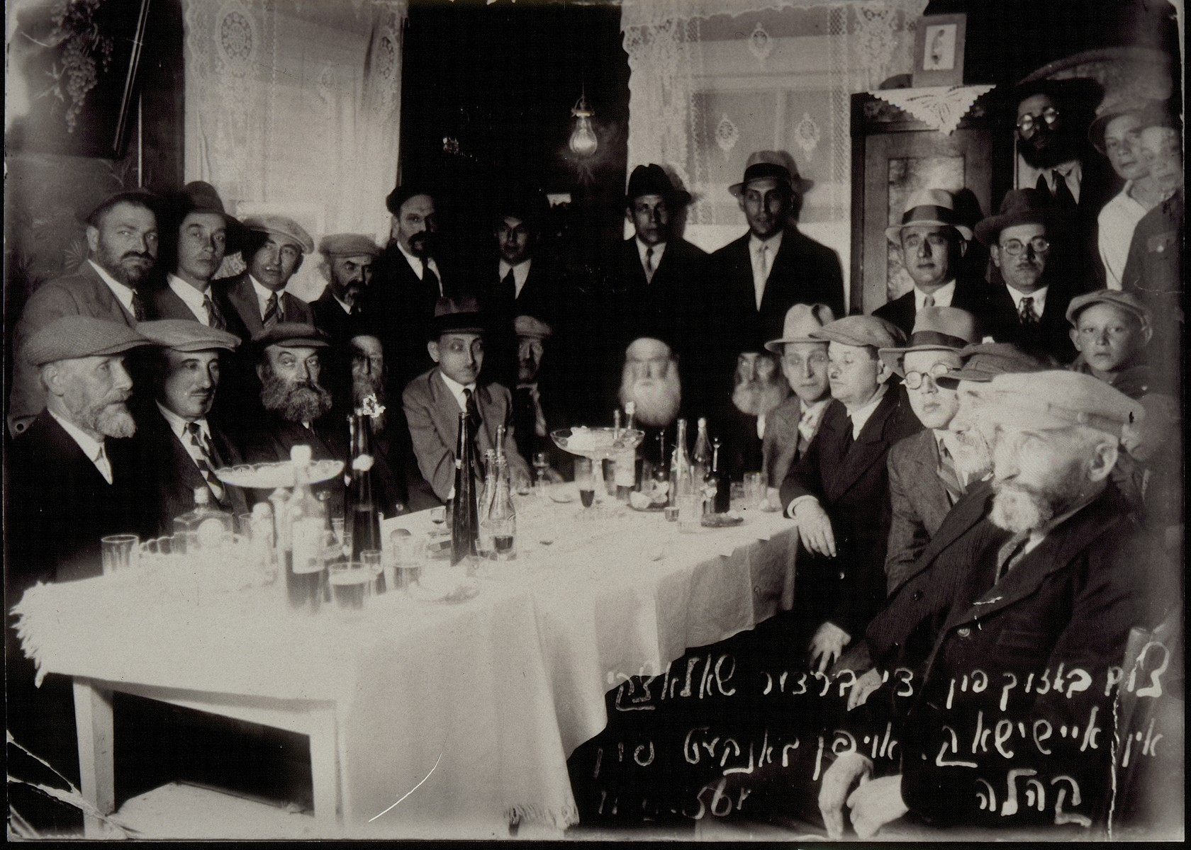 Guests at a banquet held in the Shlanski home honoring Dr. Morris Shlanski and his brother Louis, for their large donation to the Eisiskes Jewish community.  Pictured seated from left to right are: Yossl Rochowski, Avraham Dubitski, Eliyahu Bastunski, Dovid Moszcenik, Dr. Morris Shlanski, Leib Berkowicz, Rabbi Szymen Rozowski (rabbi of Eisiskes), Avraham-Mordekhai Shlanski, Louis Shlanski, Markl Koppelman; unknown, unknown and Reuven-Beinush Berkowicz.  Standing from left to right are: Baruch Matikanski, Faivl Epstein; Benyomin Tshorny, Rephael, unknown, unknown, Zelig Shlanski, Dodke Schwartz; Yudl Dwilanski and Mote Yosl Kremin.  The identity of the people in the third row is unknown.  Apart from Markl Koppelman, who was killed by members of the Polish Home Army, and the Shlanski brothers, all those pictured were killed by the Germans during the September 1941 mass shooting action in Eisiskes.