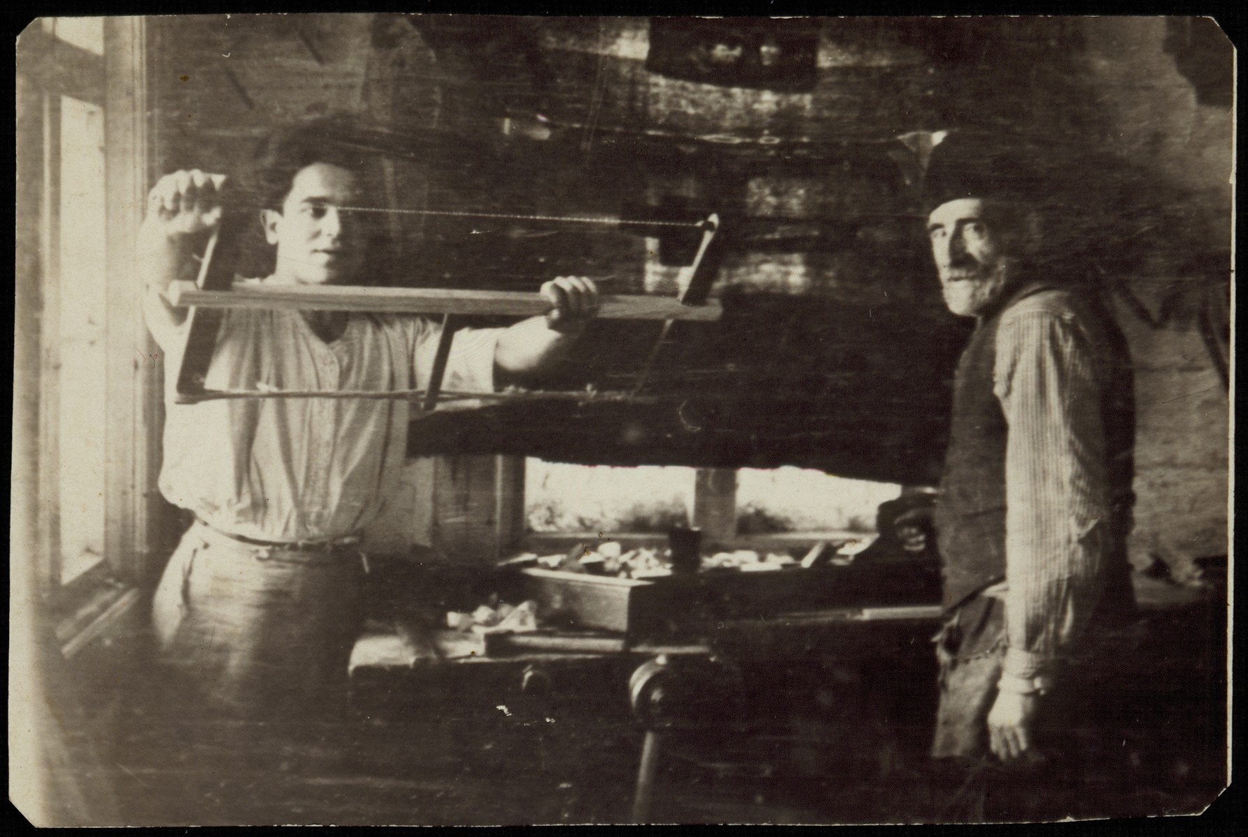 Gedalia Cofnas and his son, Pessah, work in their carpentry shop.   Gedalia was murdered by the Germans during the September 1941 mass killing action in Eisiskes, and Pessah survived in Russia.