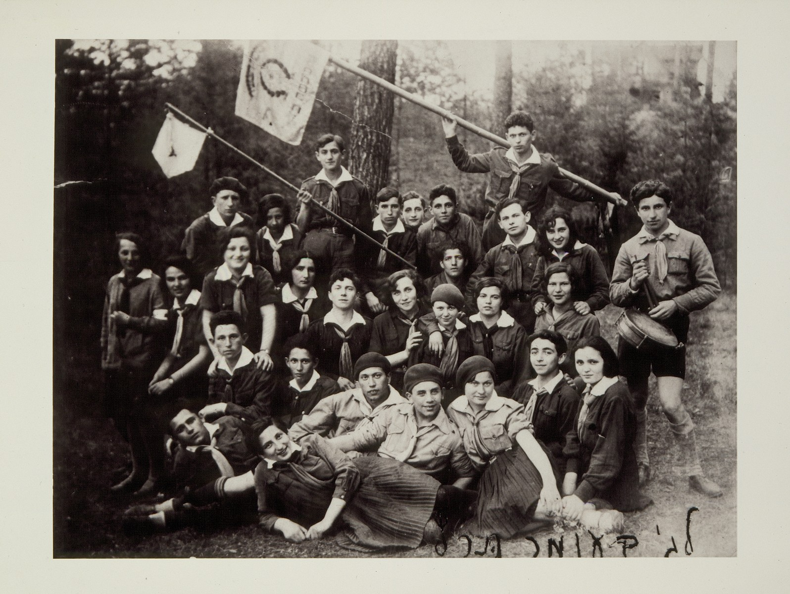 Members of Hashomer Hatzair from Eisiskes and Vilna celebrate Lag Ba'Omer on an outing in the woods.   Dov Wilenski, is standing in the top row holding a flag.  He later immigrated to Palestine.