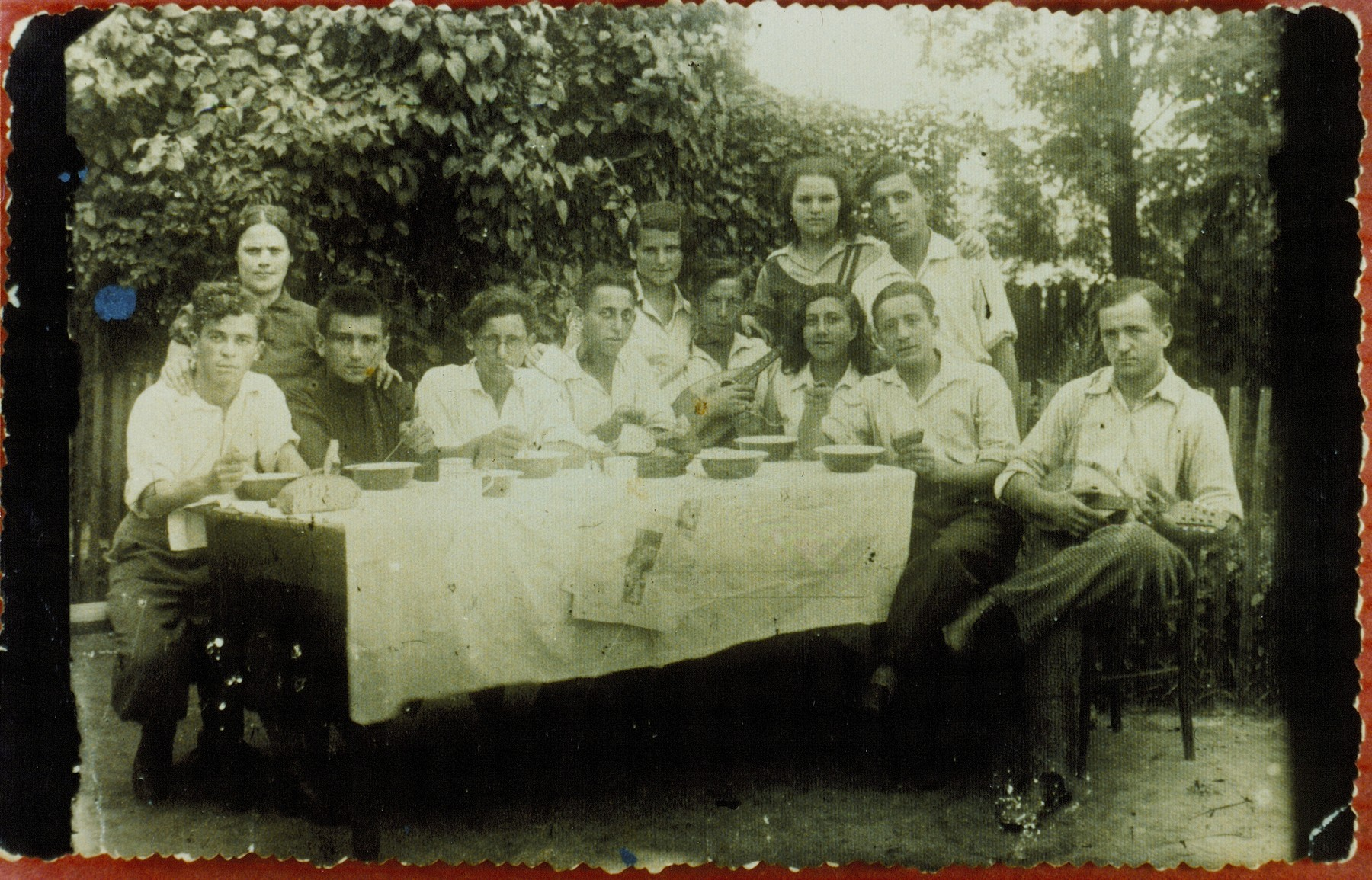 Members of a Hehalutz hachsharah gather around a picnic table set with bowls prior to their immigration to Palestine.  Matle Shuster (standing third from right) immigrated to Palestine.  The fate of the others is unknown.