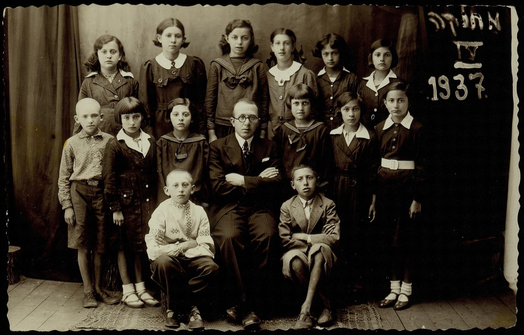 "Fourth grade class picture.   (first row) Avigdor Katz (left ) and Yankele Kaganovicz; (second row, right to left) Sheinele Dwilanski, (first name unknown)  Bichwid, Hayya Shlanski, Hebrew teacher Mr. Okun, (first name unknown) Narodowicz, (name unknown), Leibke Portnoy;  (top row, right to left) name unknown, Leah Michalowski, ""The Rubishker"", Altke Koutsai, Masha Dubczanski, Rachel Koppelman.    Hayya immigrated to America, Rochke Koppelman was killed by the Polish Home Army; the others were murdered in the September 1941 massacre."
