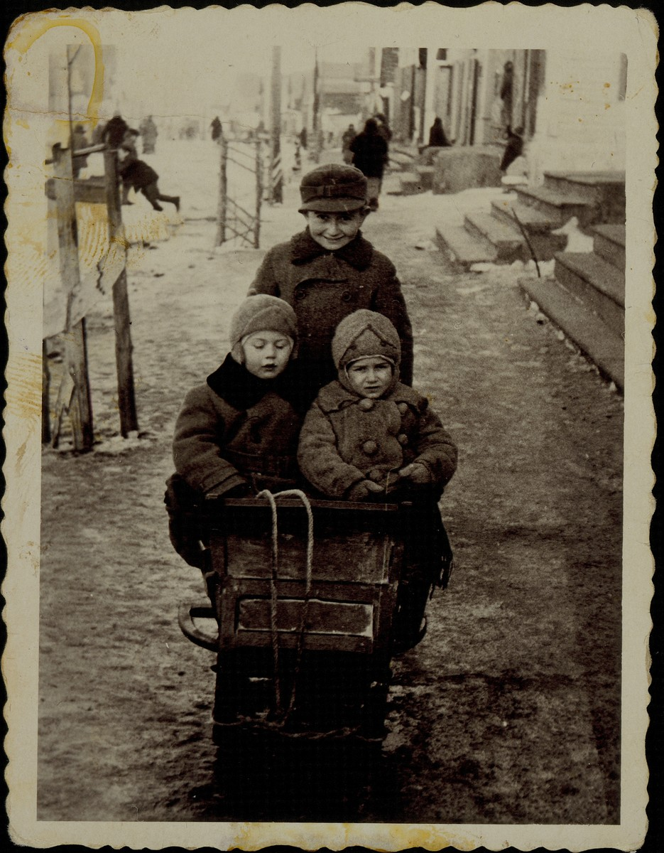 Three young children go for a sled ride on a snowy street in Eisiskes.  Liebke (Leon) Shlanski is standing behind his sister Sara (right) and the grandson of Rabbi Szymen Rozowski (left). Sara and Leibke immigrated to America. The grandson of Rabbi Rozowski was murdered in the September 1941 massacre.