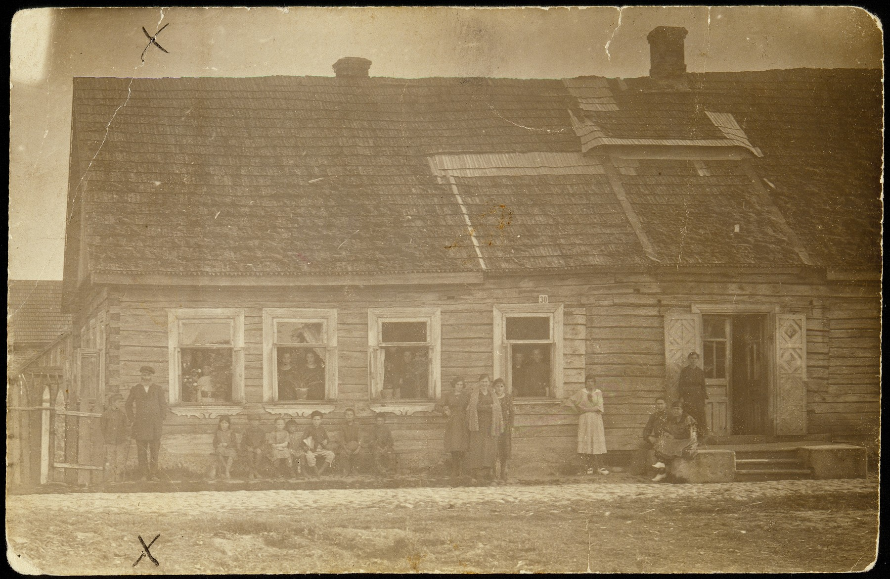 Members of the Lubetski family stand outside their house.  The two squares on the roof are the hinged rooftops that were opened for the holiday of Sukkot.  The open space was covered with fresh branches (skhakh), and the room beneath became the sukkah.
