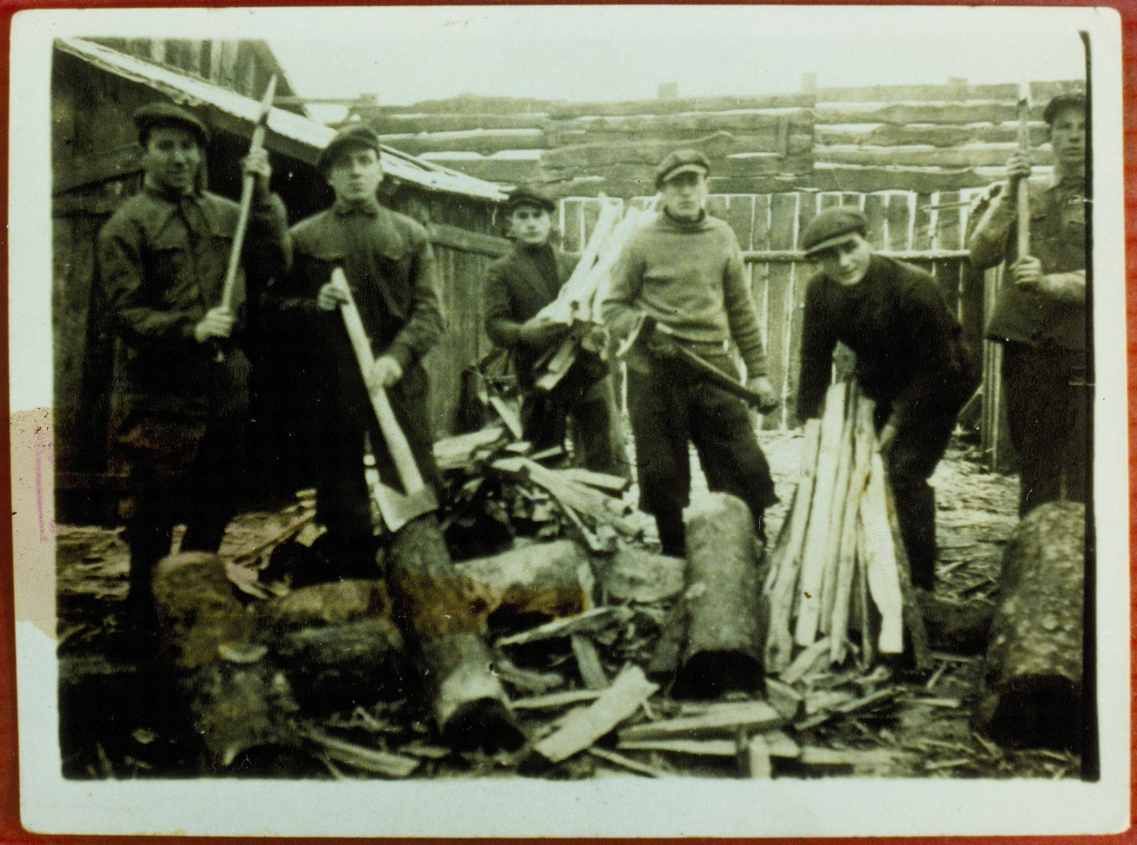 Members of a kibbutz hachshara from chop wood in a lumberyard.