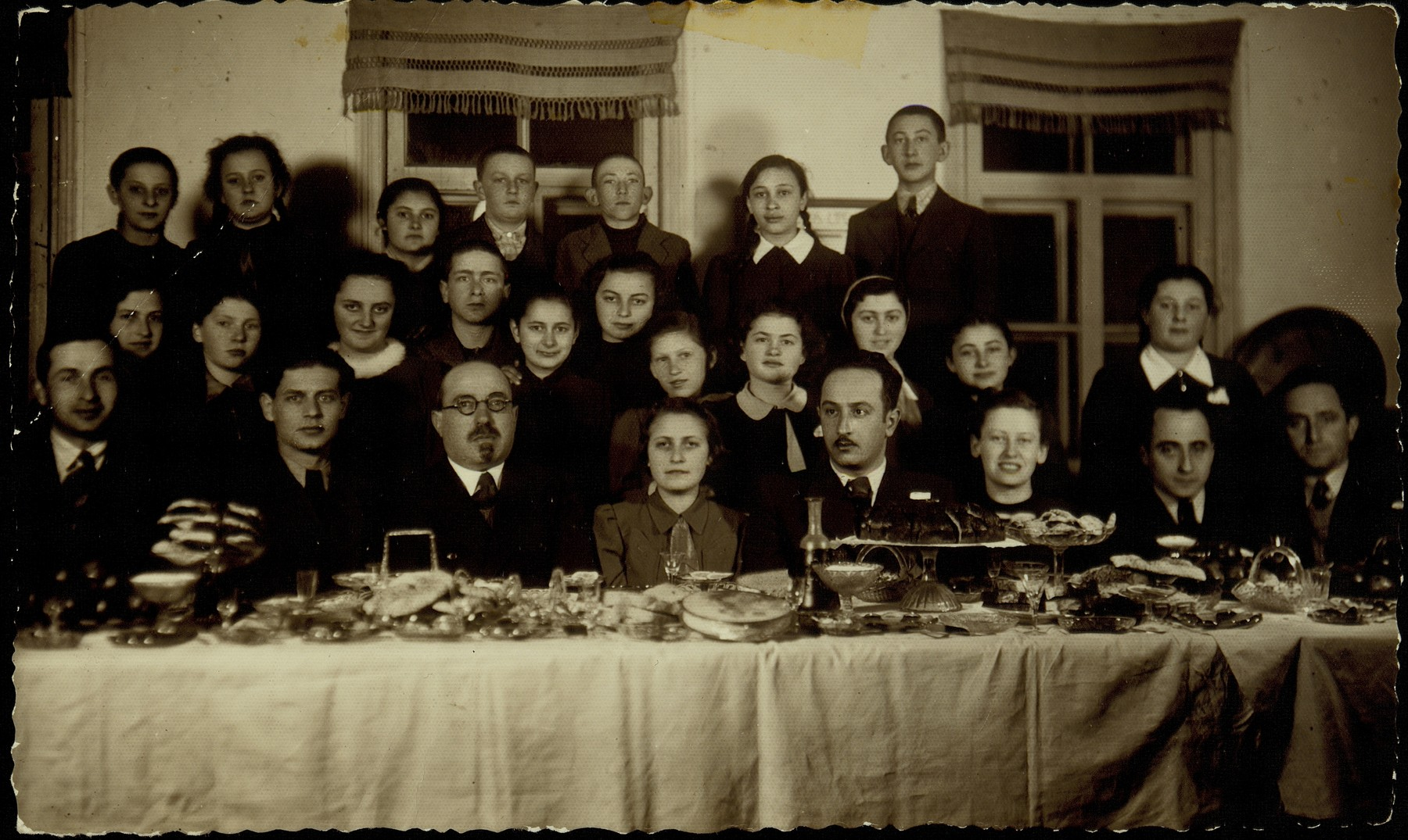 Hayya Shlanski celebrates her impending immigration to America at a party in her honor.  Teachers sitting (from left to right). Gabi, Perski (uncle of Israel's former  Prime Minister Shimon Peres), Botwinik, student Hayya Shlanski, new Jewish Lithuanian principal of school, name unknown, Kahn ( lived in Bastunski house), Patashnik. Top row (from right to left): Avigdor Katz, Devorah, Avremeke Schmidt, unknown, Rachel Koppelman. Second row (fifth from left) is Sheinele Dwilanski. Standing to the far right in the second row is Etke Wilenski.