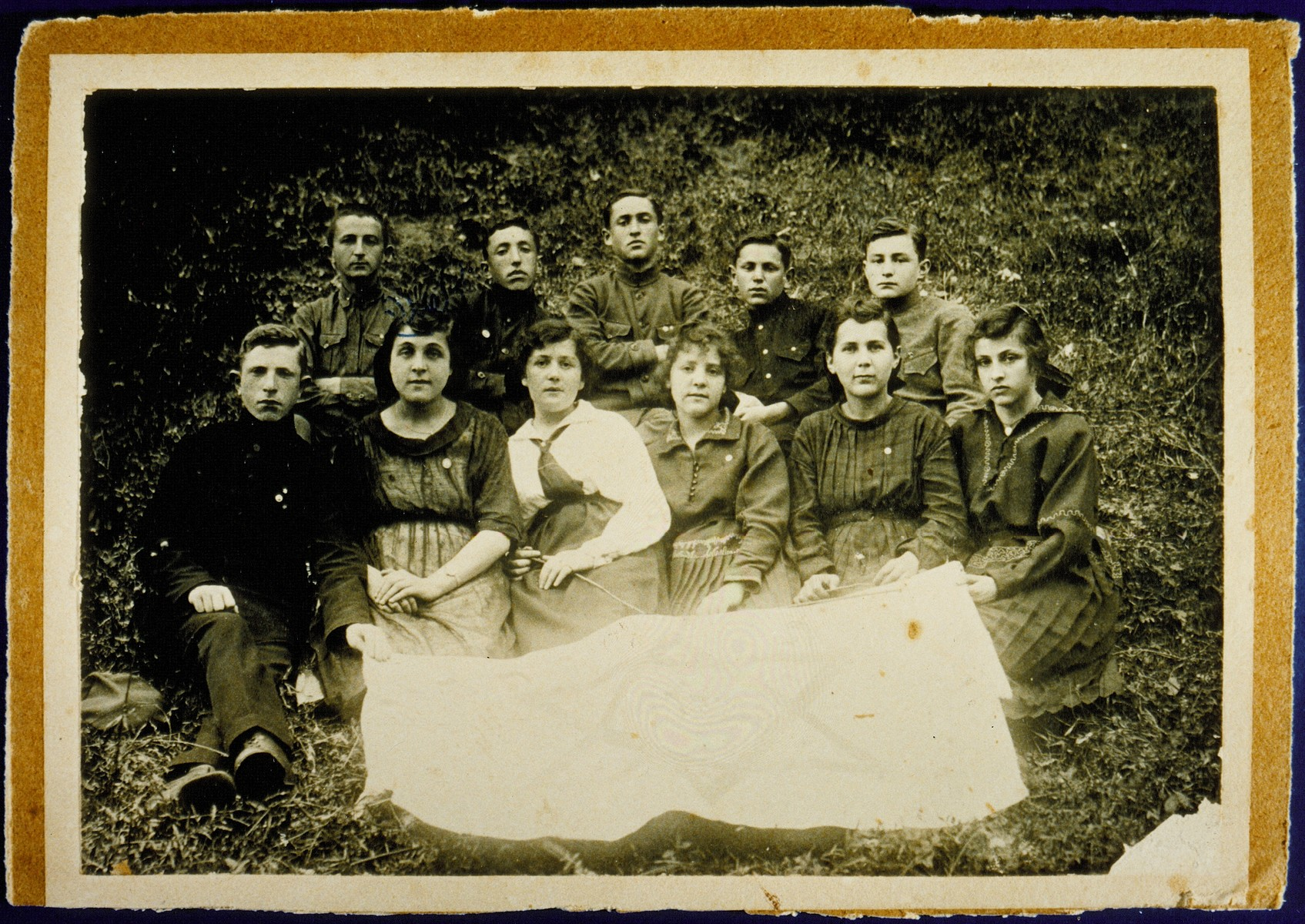 Members of the Zionist group Herut ve-Tehyia (Freedom and Revival) pose in front of the group's banner.     Front row from right to left: Itta-Malka Pachianko, Esther Dwilanski, Zipporah Nochomowicz, Hannah Koppelman, Zipporah Lubetski Tokatli and Shlomo Cofnas.  Top row from right to left: Peretz Kaleko, Shaul Schneider, Zeev Kaganowicz, Shlomo Kiuchefski and Shalom Sonenson.    Zipporah Lubetski Tokatli, Hannah Koppelman, Shaul Schneider and Peretz Kaleko immigrated to Palestine. Zipporah Nochomowicz immigrated to South America.  Shalom Sonenson  survived the Holocaust in hiding.  Itta-Malka Pachiano was murdered during the Holocaust.  Shlomo Kiuchefski was murdered by members of the Polish Home Army.