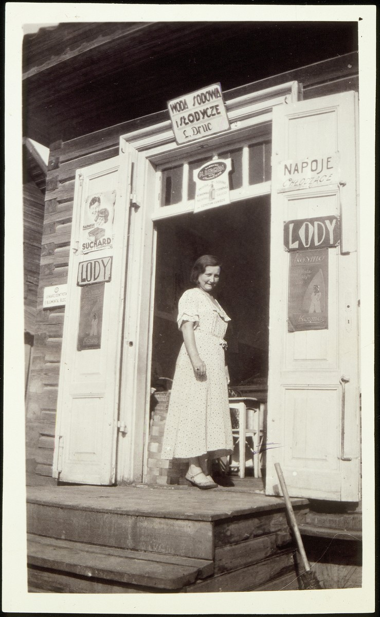 A woman stands by the entrance to a general store.